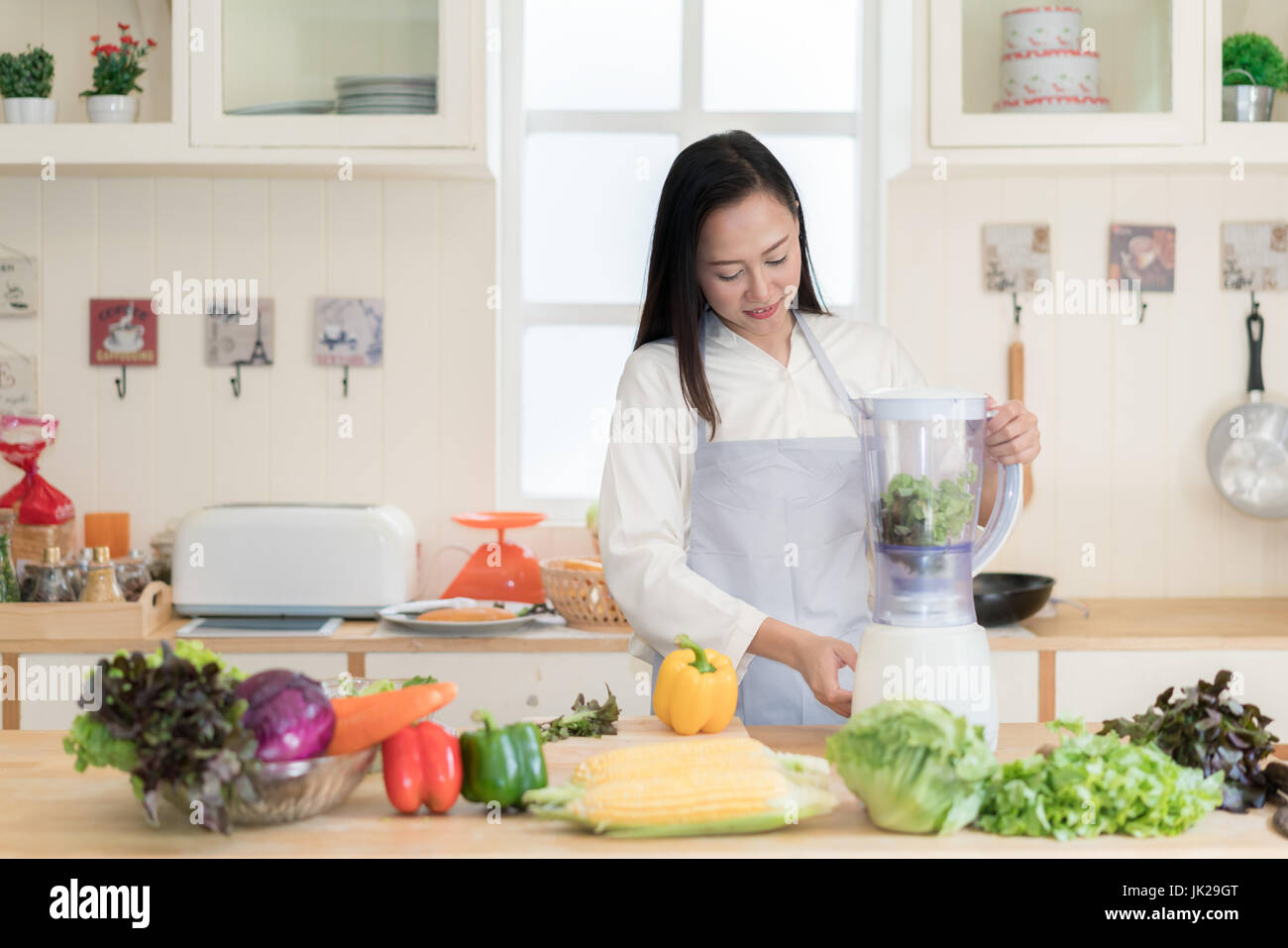 Vegetable smoothie. Asian woman making green smoothies with blender home in kitchen. Healthy raw eating lifestyle - Stock Image