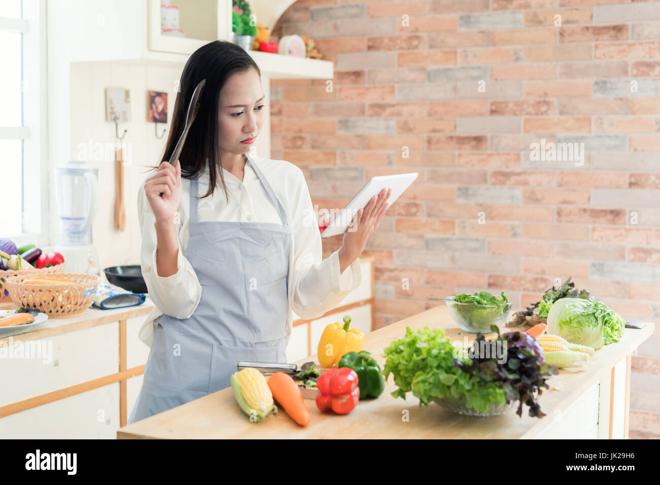 Cheerful Asian young woman is cooking in the kitchen with joy. She is standing and holding digital tablet of recipe. - Stock Image