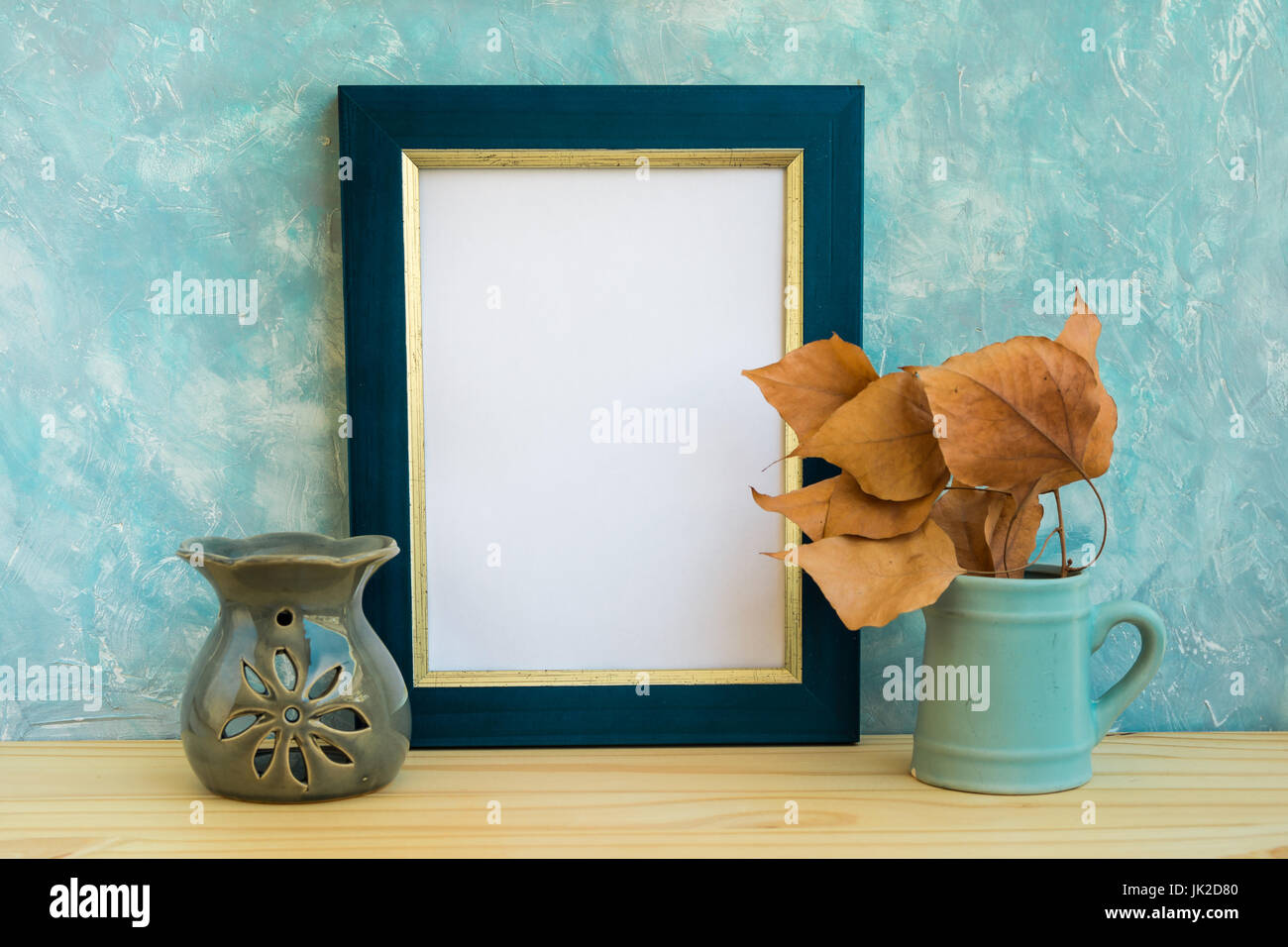 Blue and golden frame mockup, concrete wall background, wood table, fry leaves, aroma therapy lamp, autumn, fall, - Stock Image