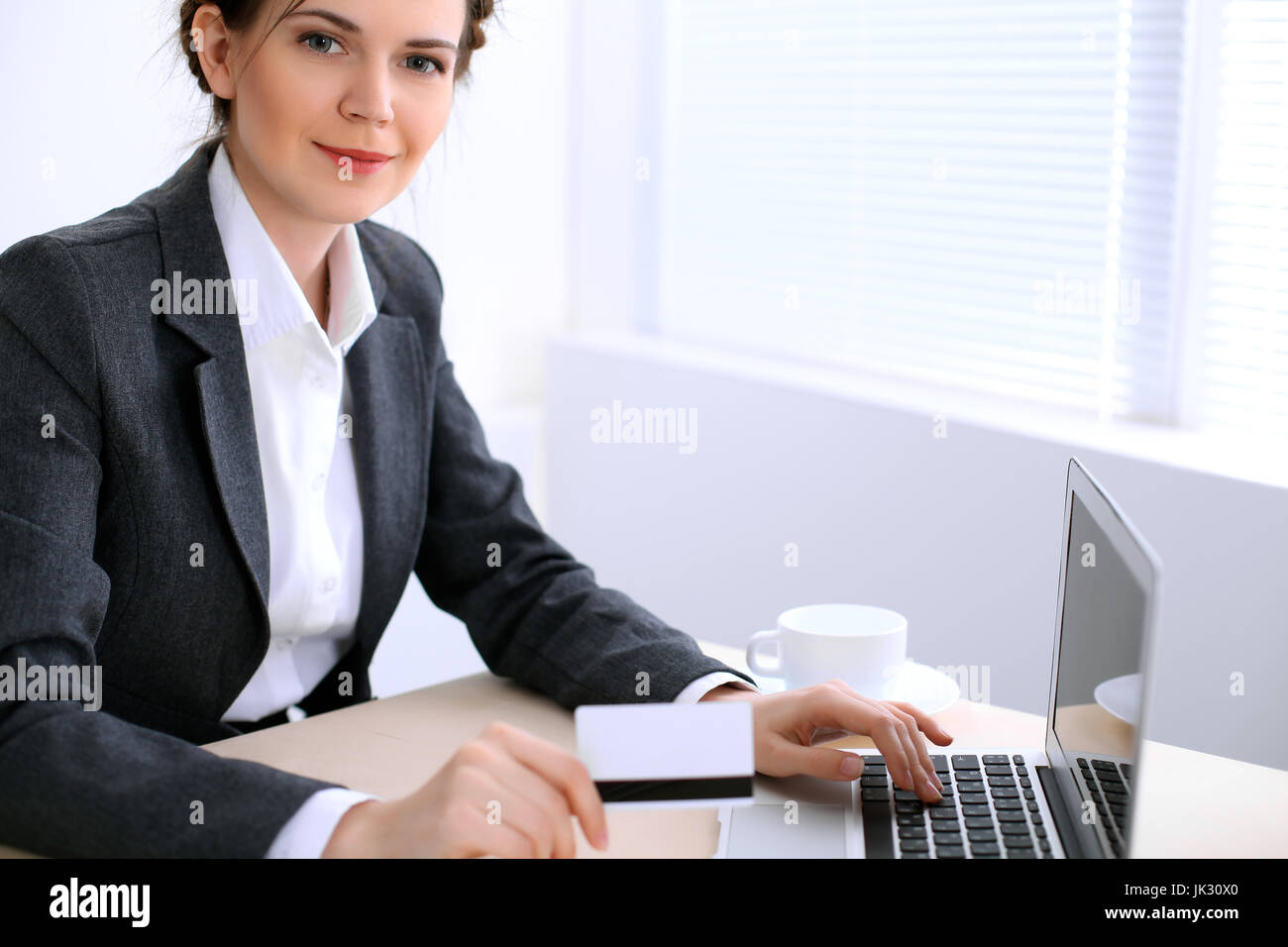 Business woman looks like yulia tymoshenko is sitting at the table and working in  white colored office . Ukrainian Stock Photo