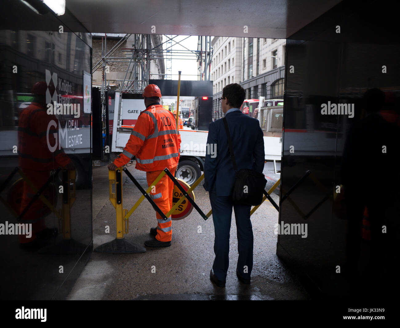 Traffic marshall on Bloomberg building site London operating safety gates  to prevent pedestrians getting injured - Stock Image