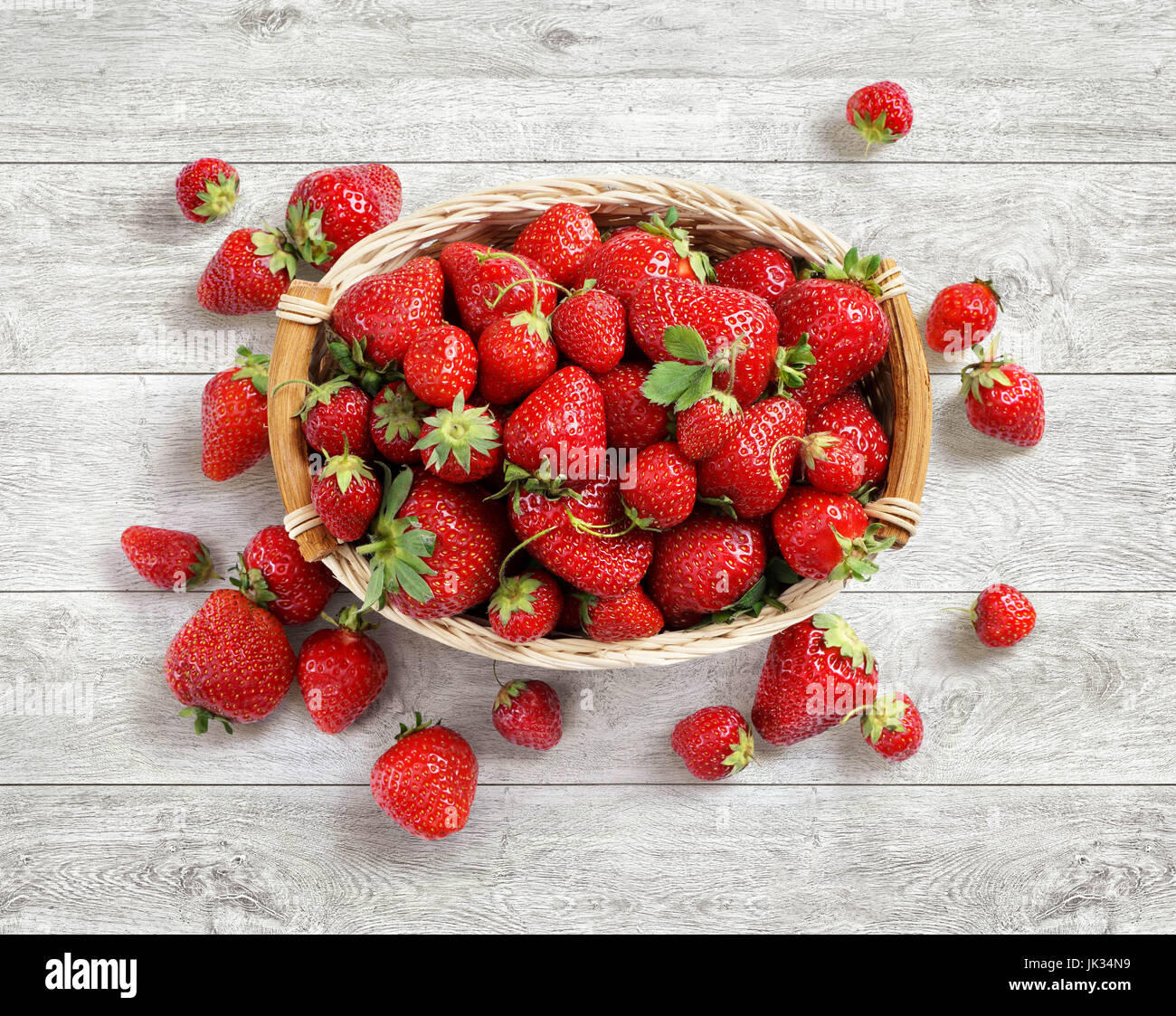 Fresh strawberry in basket on white wooden background. Top view. High resolution. Harvest Concept - Stock Image