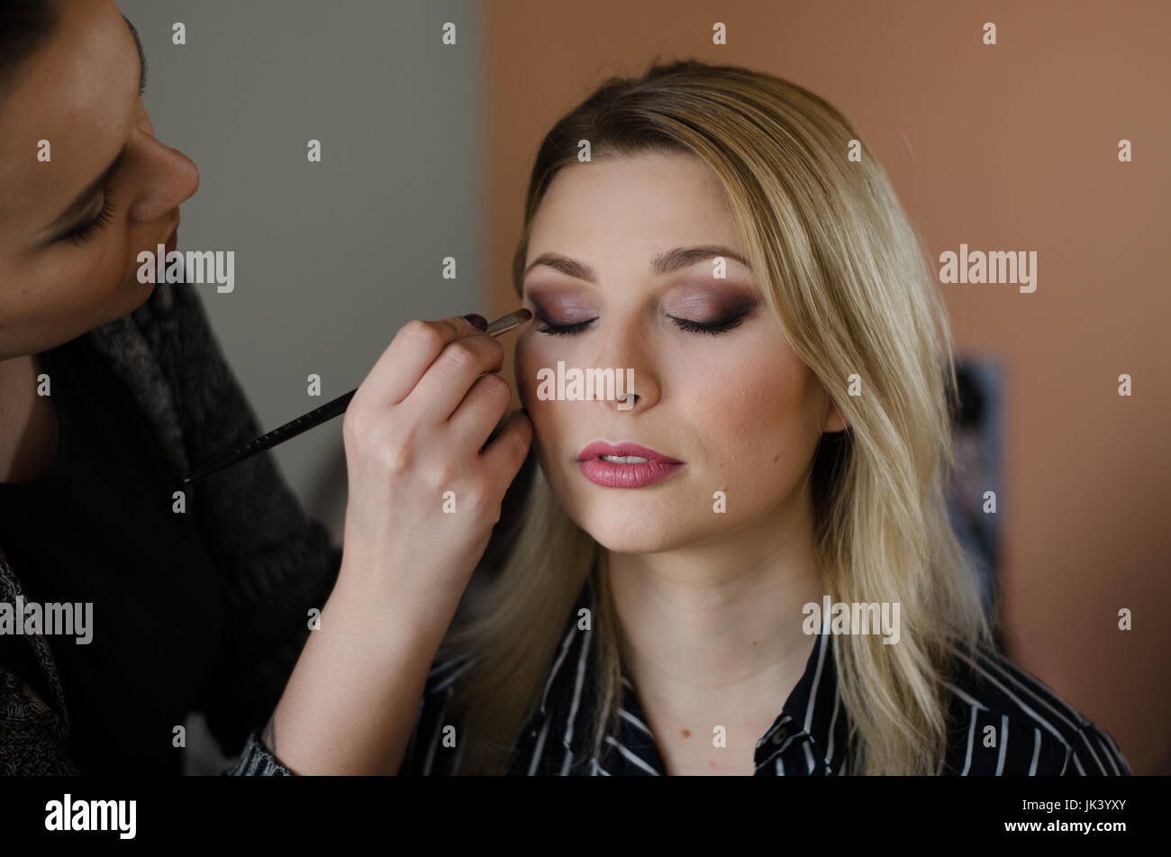 Young beautiful woman having her make up done by a make up artist - Stock Image