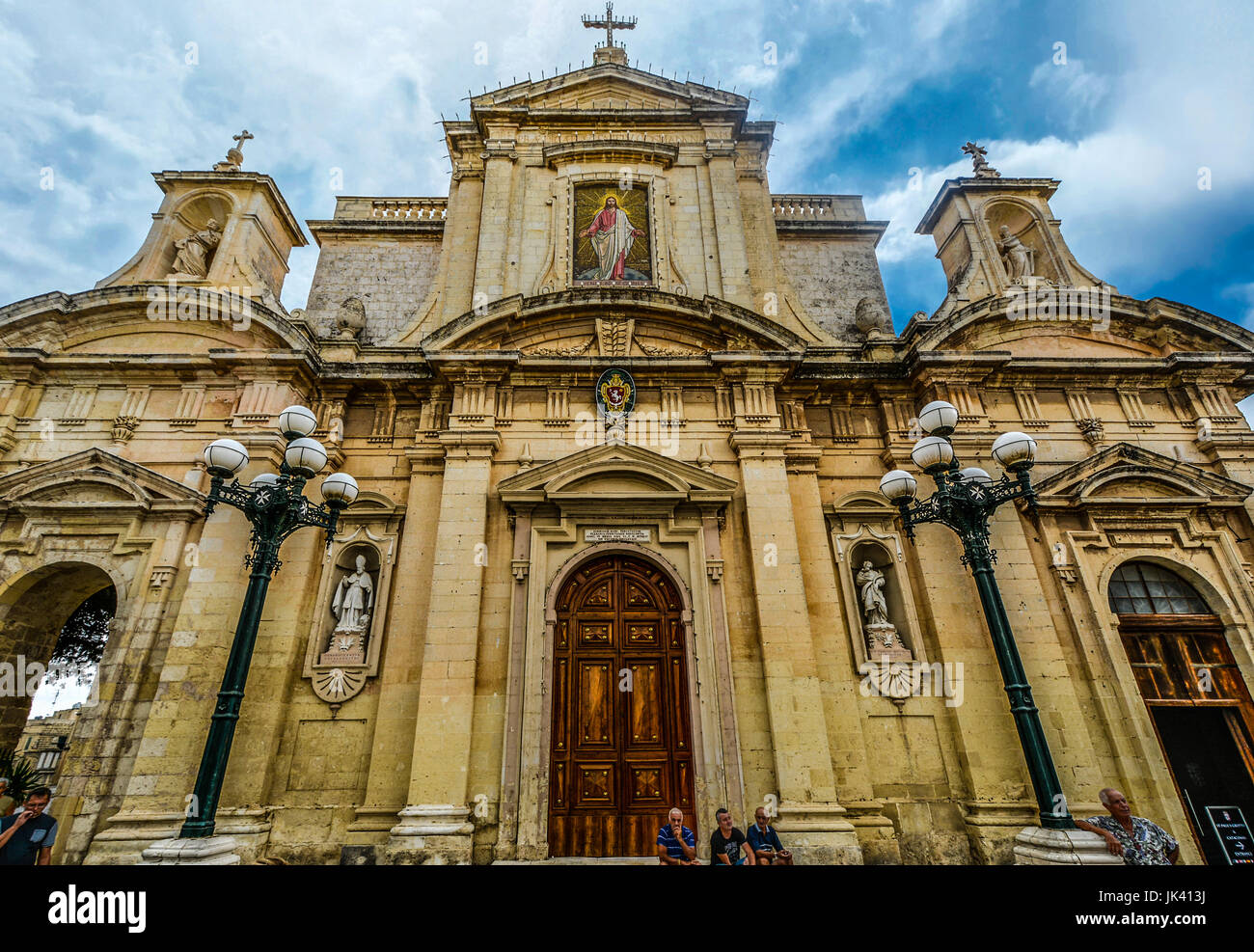 Gothic church or cathedral in the ancient city of Mdina on the Mediterranean island of Malta with locals sitting - Stock Image