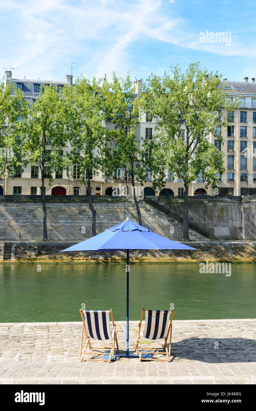 Two blue and white striped deck chairs under a blue parasol on the bank of the river Seine with poplar trees and Stock Photo