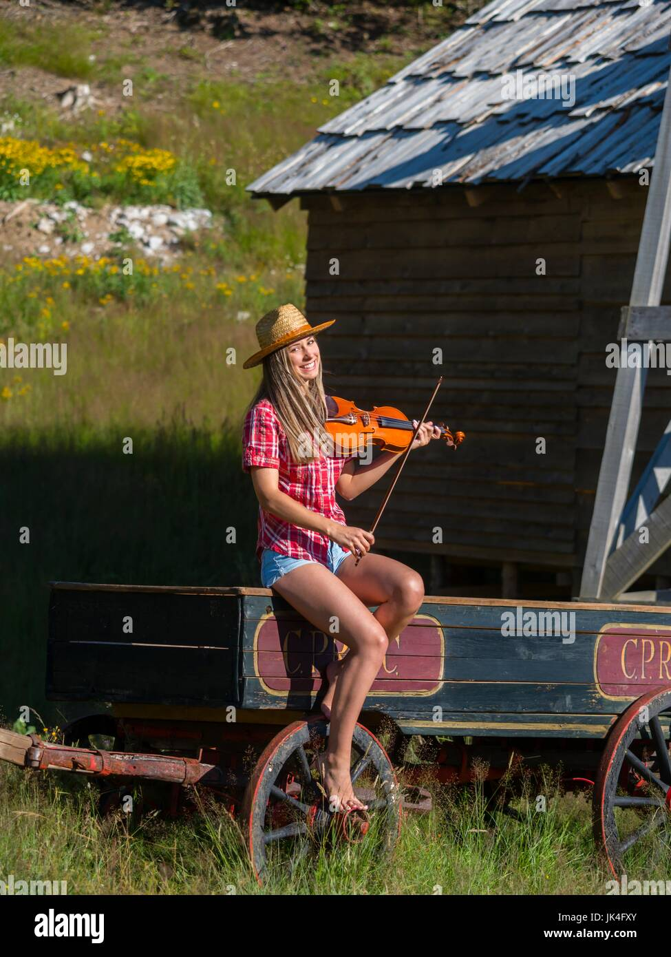 Country-girl musician playing violin sitting atop horse-drawn wagon looking laughing smiling at camera womans apparently - Stock Image