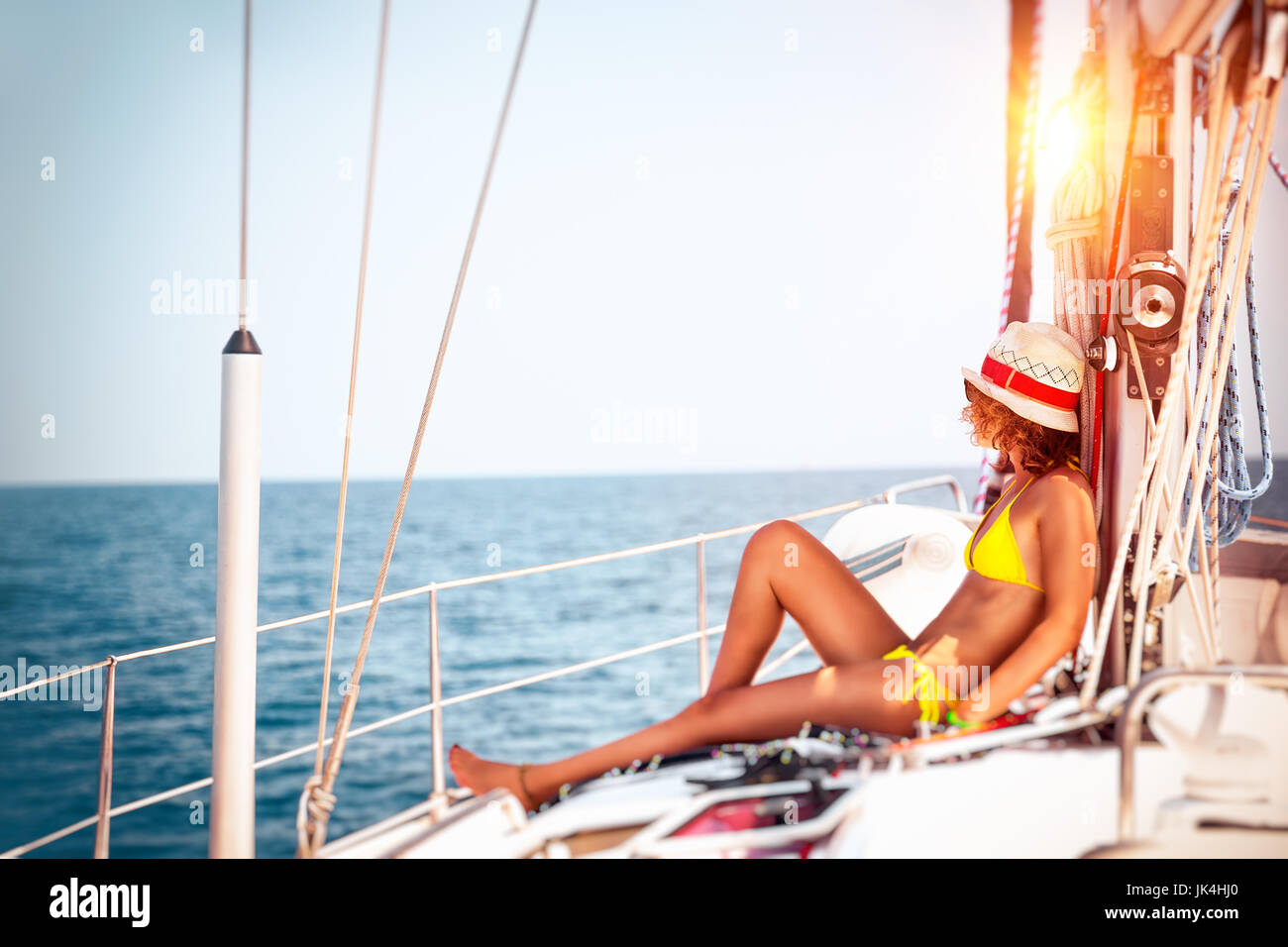 Woman relaxing on sailboat, slim model tanning on the deck of the yacht in bright sunny day, enjoying sailing adventures, - Stock Image