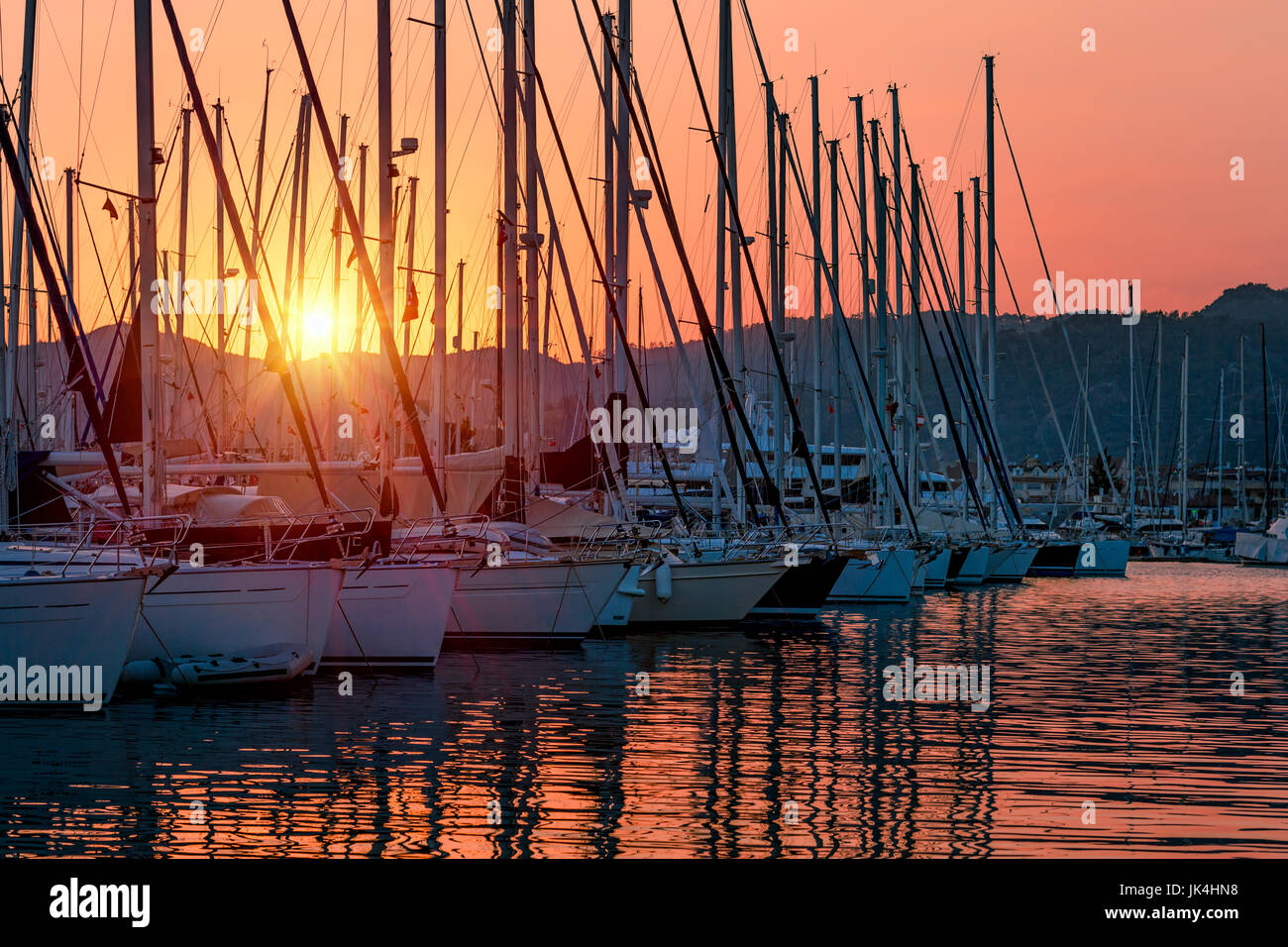 Sailboats in the harbor in mild sunset light, beautiful view on the luxury water transport in the dock, summer vacation - Stock Image