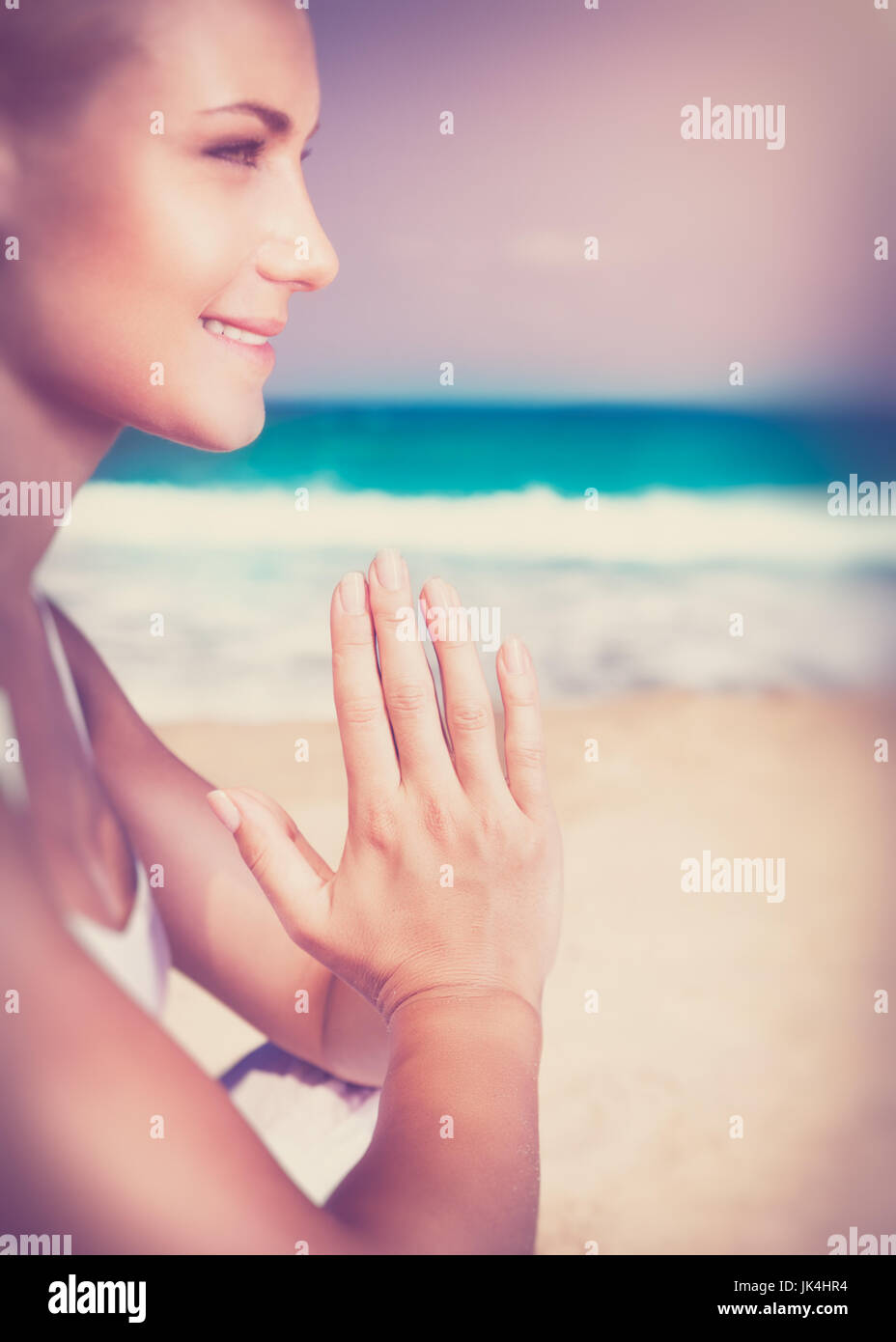 Beautiful woman sitting on the beach and meditating, harmony of soul, happy healthy life - Stock Image