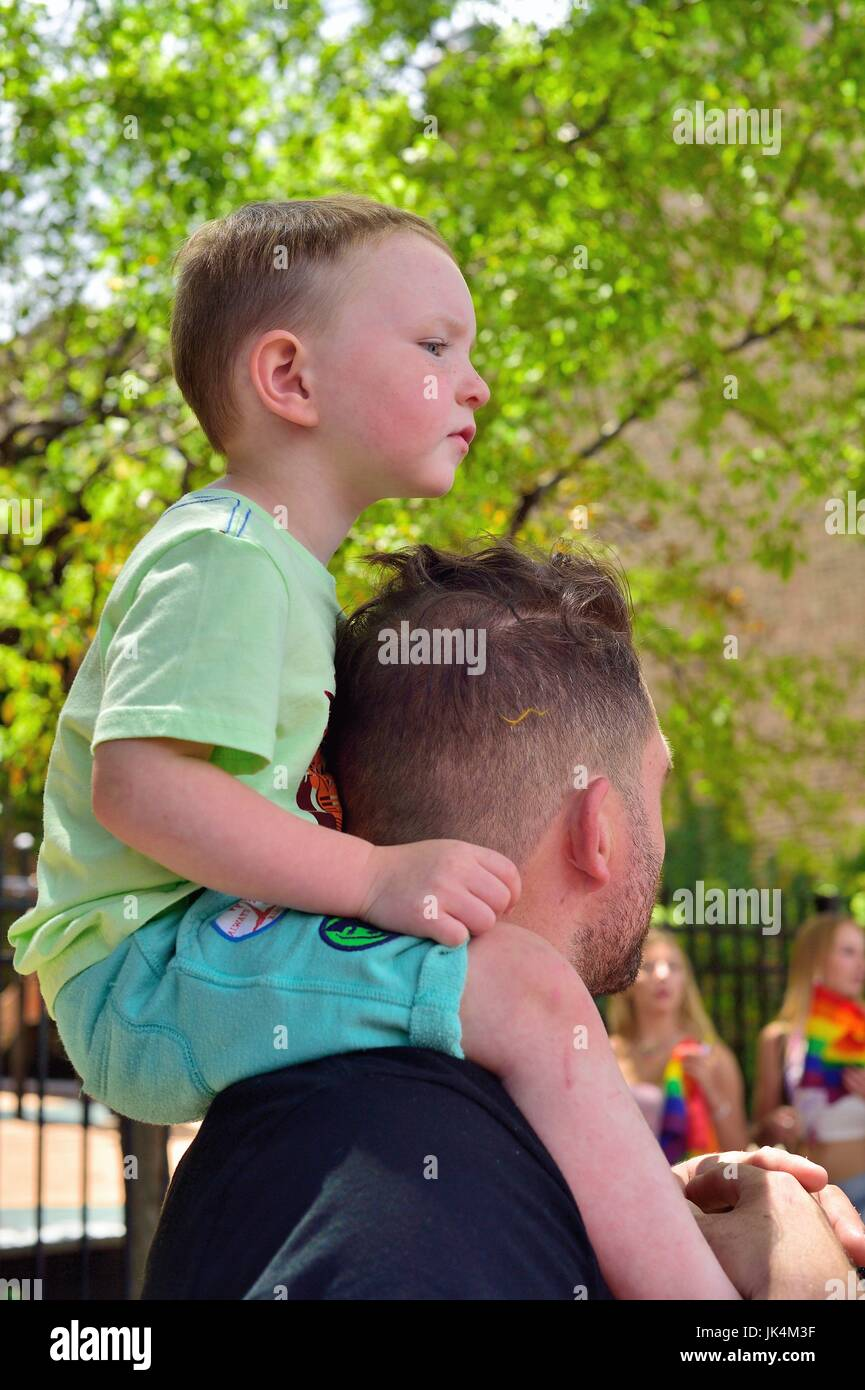 Young boy getting an elevated view of Chicago's Gay Pride Parade. The parade is held each June on the city's - Stock Image