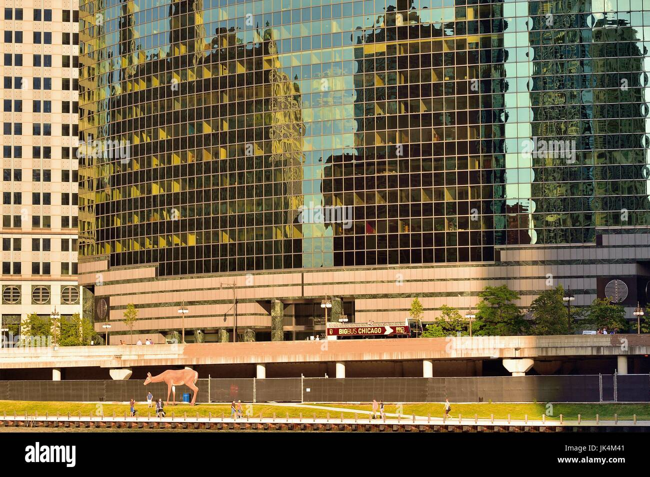 A larger-than-life sized white tail deer sculpture gracing the Chicago Riverwalk in front of the sleek 333 Wacker - Stock Image