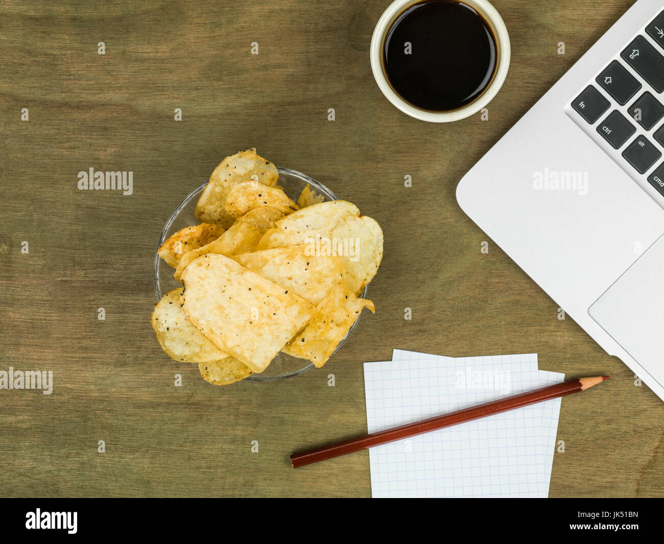 Computer Workstation With a Boewl of Potato Crisps or Potato Chips With a Cup of Black Coffee - Stock Image