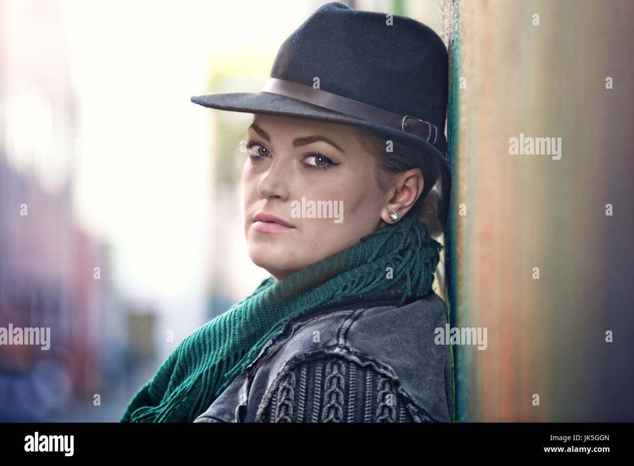 Closeup portrait of a fashionable, 30-something woman leaning against a wall - Stock Image