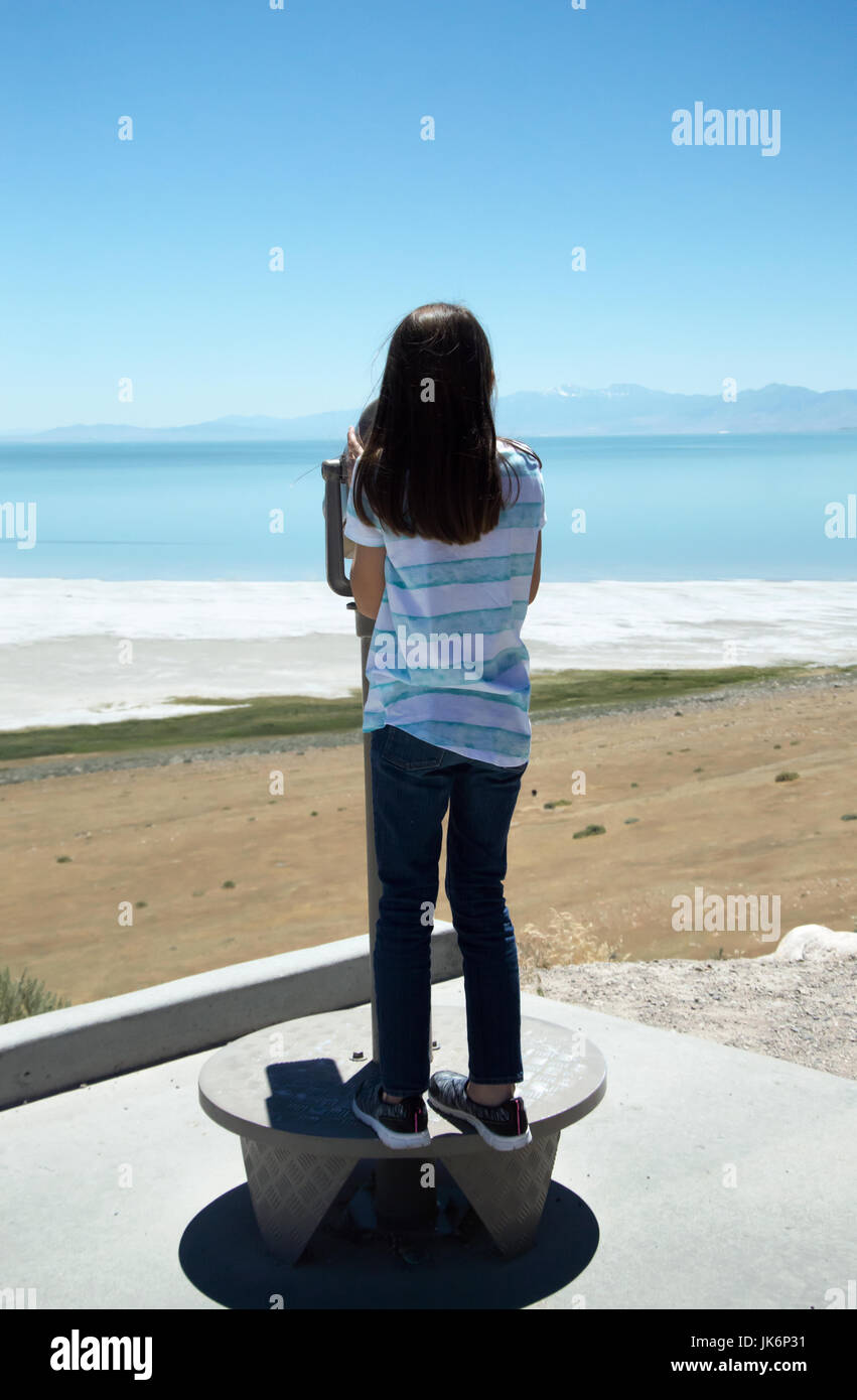 A young girl looking through a coin operated binoculars at the Great Salt Lake on Antelope Island. - Stock Image