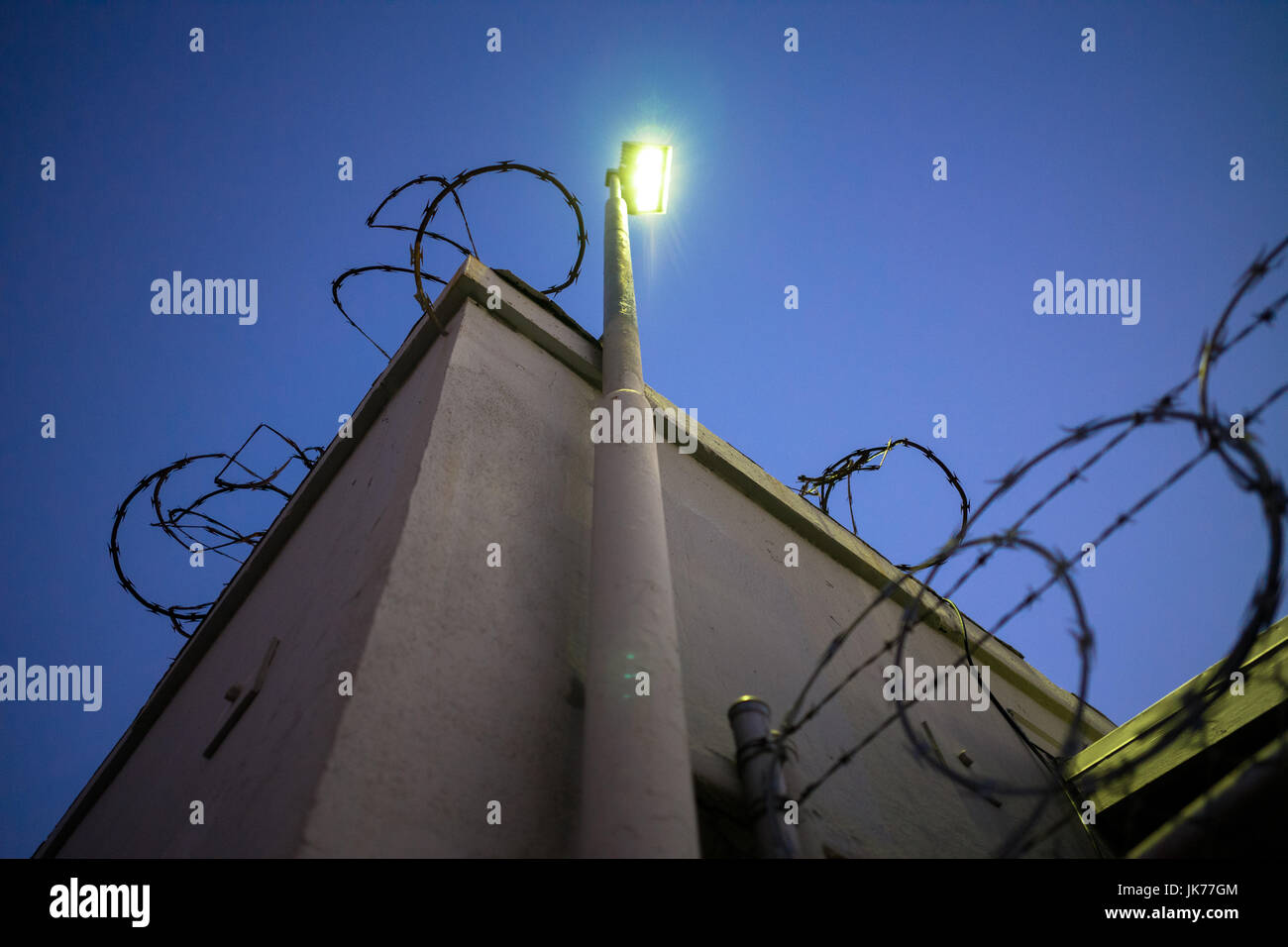 Fence and building protected by barb wire at night. - Stock Image