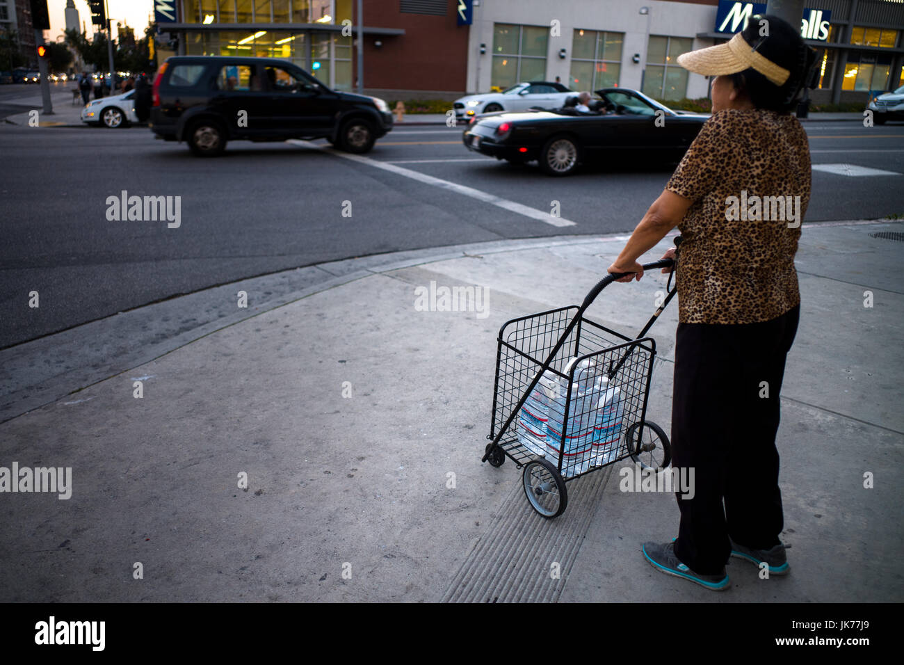 During a heat wave, an older immigrant woman transports a cart of water bottles at an intersection in Los Angeles, - Stock Image
