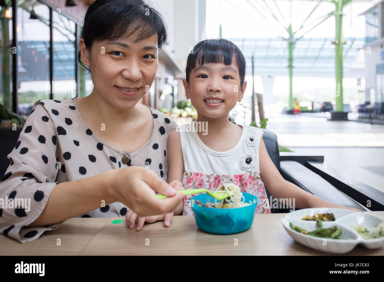 Asian Chinese mother and daughter eating beef noodles in outdoor cafe - Stock Image