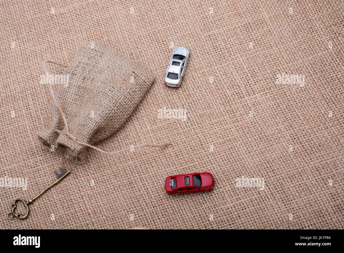 Key, toy cars, human figures and a sack on a canvas - Stock Image