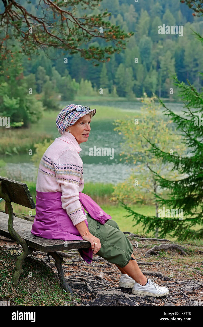 Woman resting on bench at lake Lautersee, Werdenfelser Land, Bavaria, Germany | Frau rastet auf Bank am Lautersee, - Stock Image