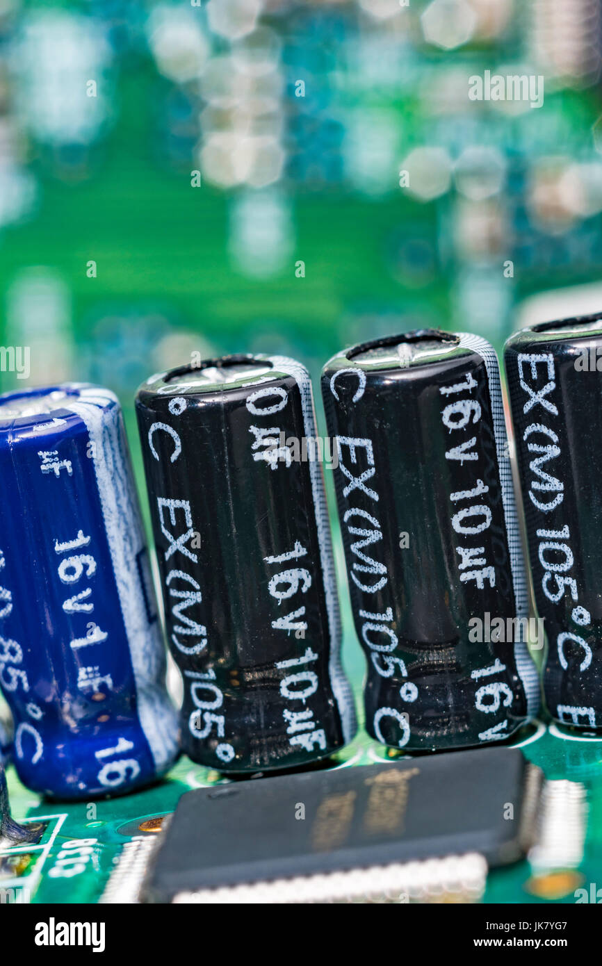 Close up of electrical capacitors on a green printed circuit board (pcb). - Stock Image