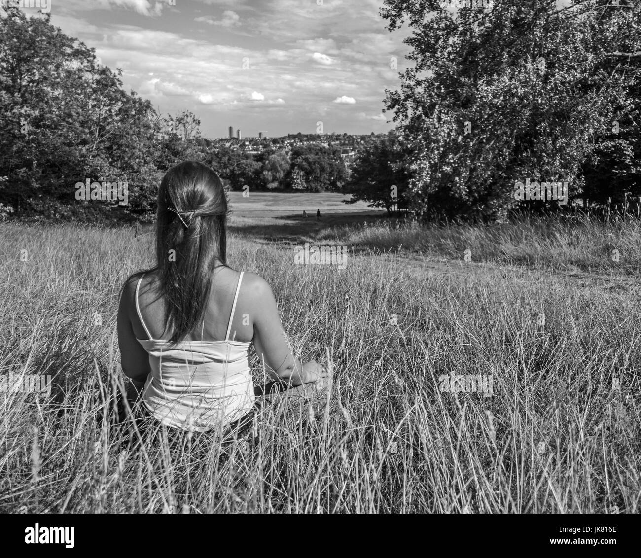 Young woman sitting meditating in grass looking toward a city - Stock Image
