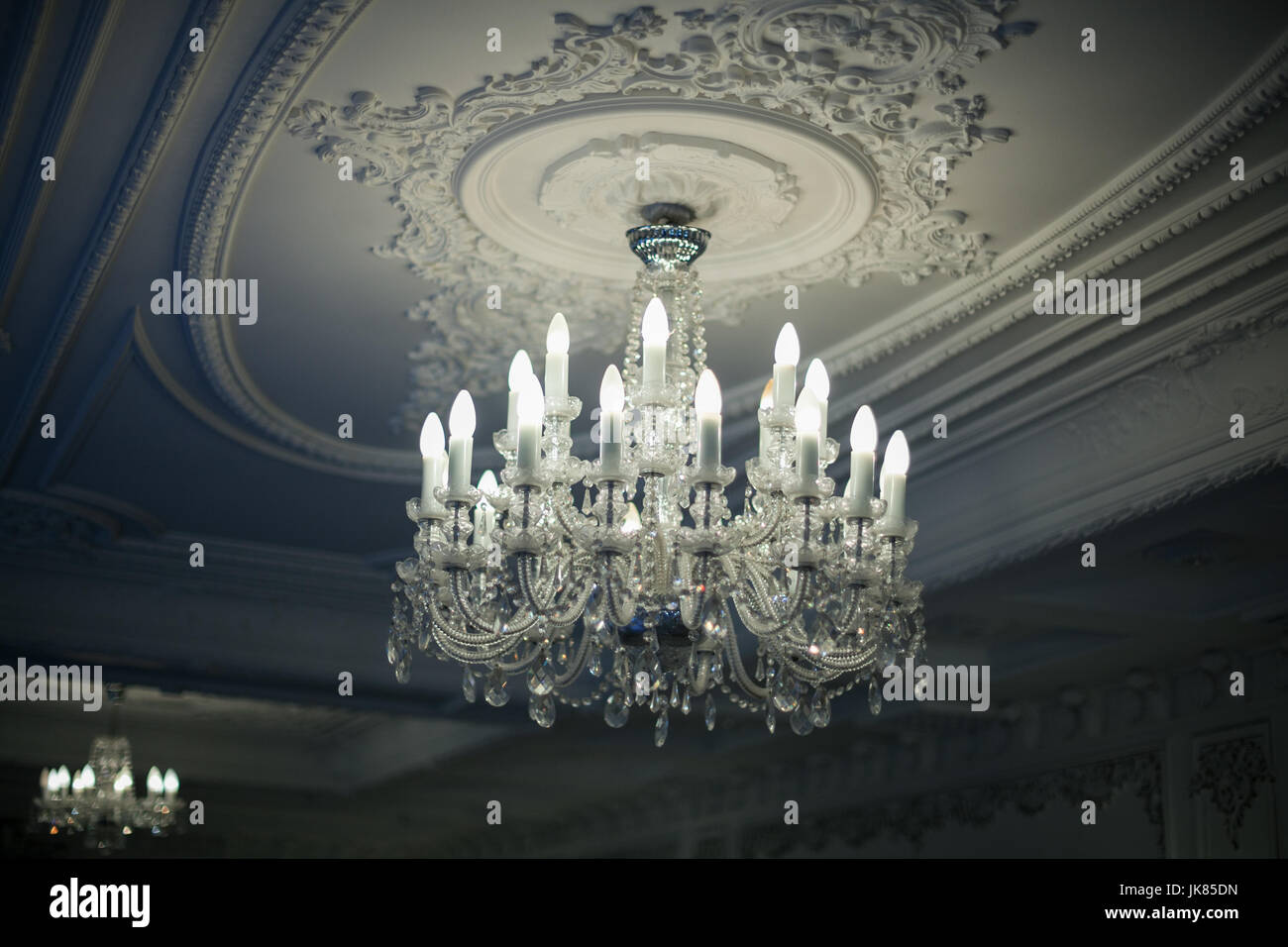 Beautiful antique crystal chandelier hangs from the ceiling in the shadows - Stock Image