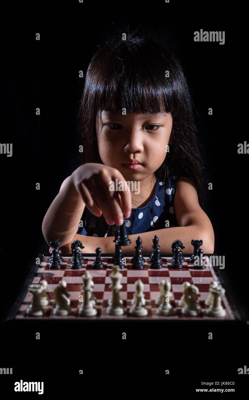 Asian Little Chinese girl playing chess in isolated black background - Stock Image