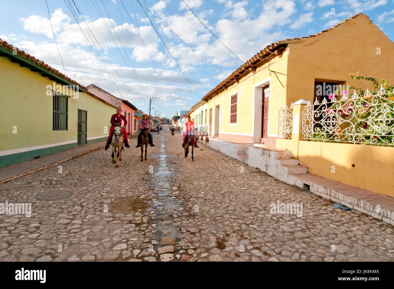 Boys riding horses down cobblestone street in Trinidad Cuba - Stock Image