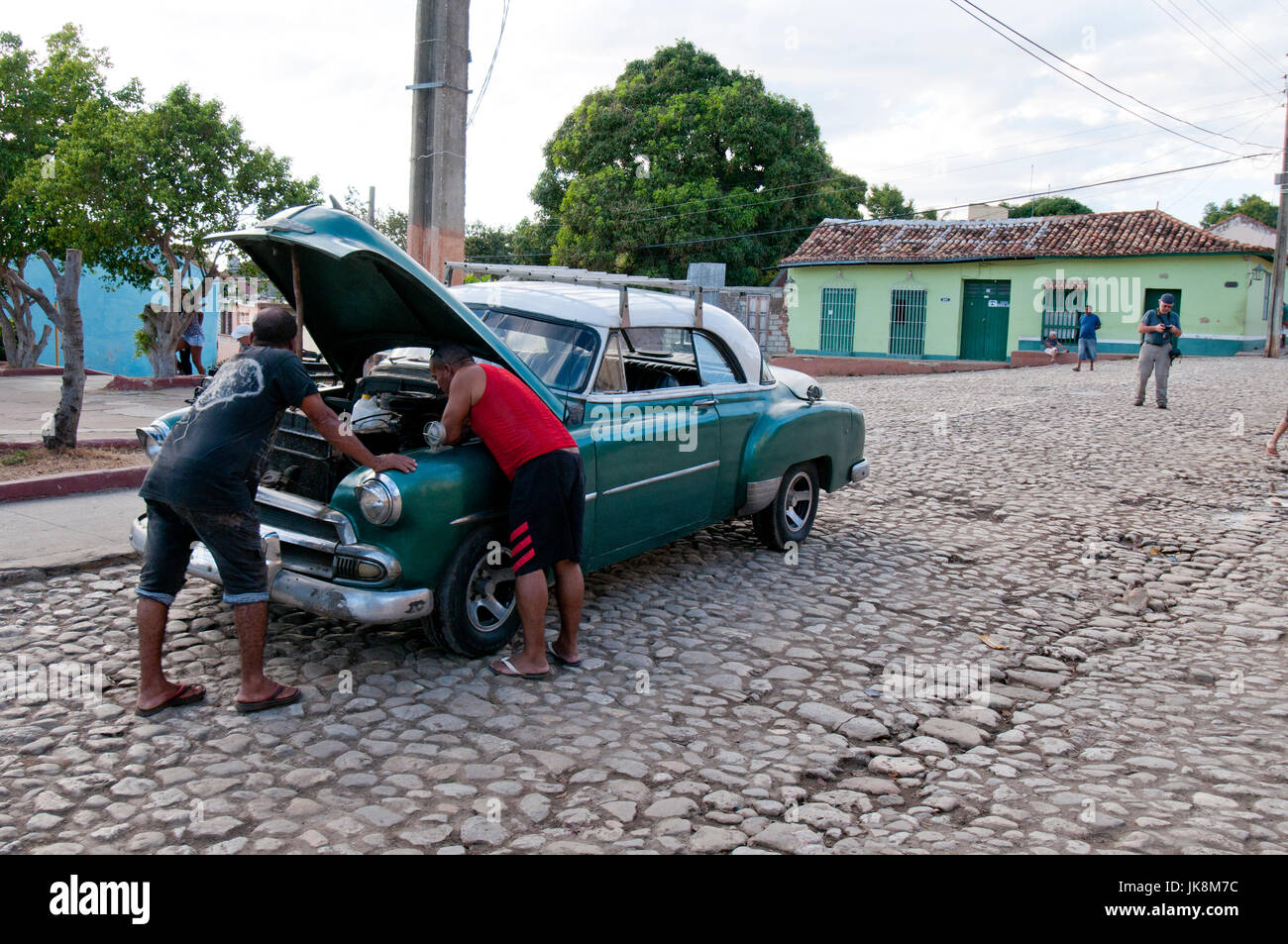 Cuban men working on broken-down old 1950's American car in Trinidad Cuba - Stock Image
