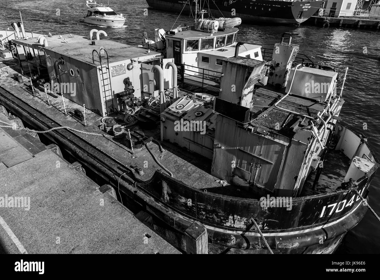 Rusty old fuel barge moored alongside with modern tug - Stock Image
