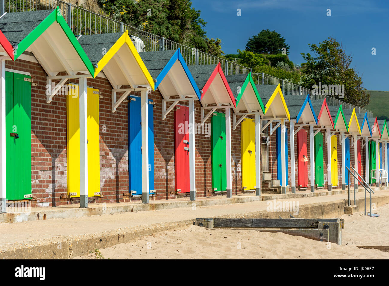 Row of colourful beach huts on a sunny day - Stock Image