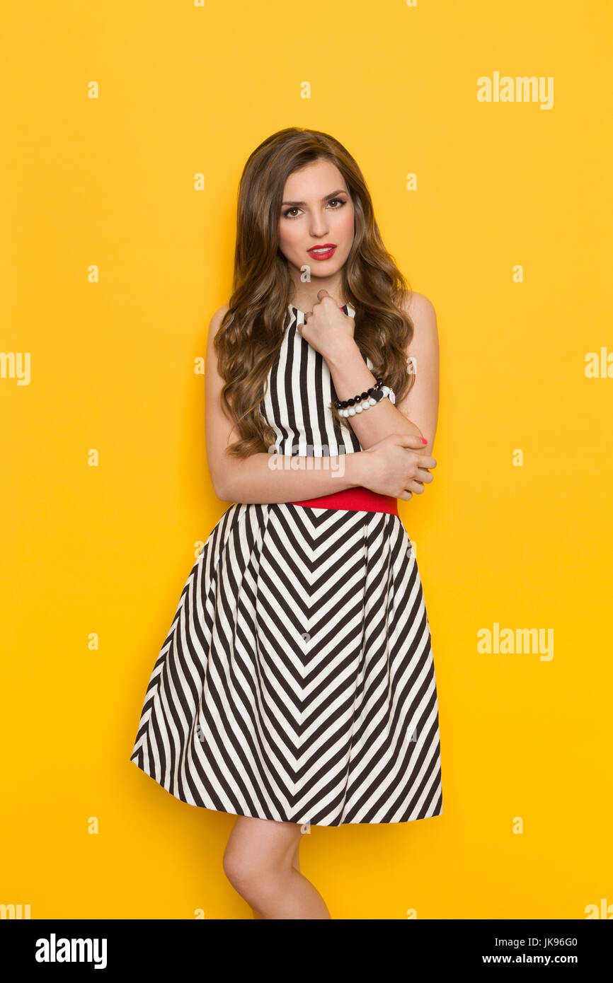 68e9d5acaba Beautiful young woman in black and white striped dress posing and looking  at camera. Three quarter length studio shot on yellow background.