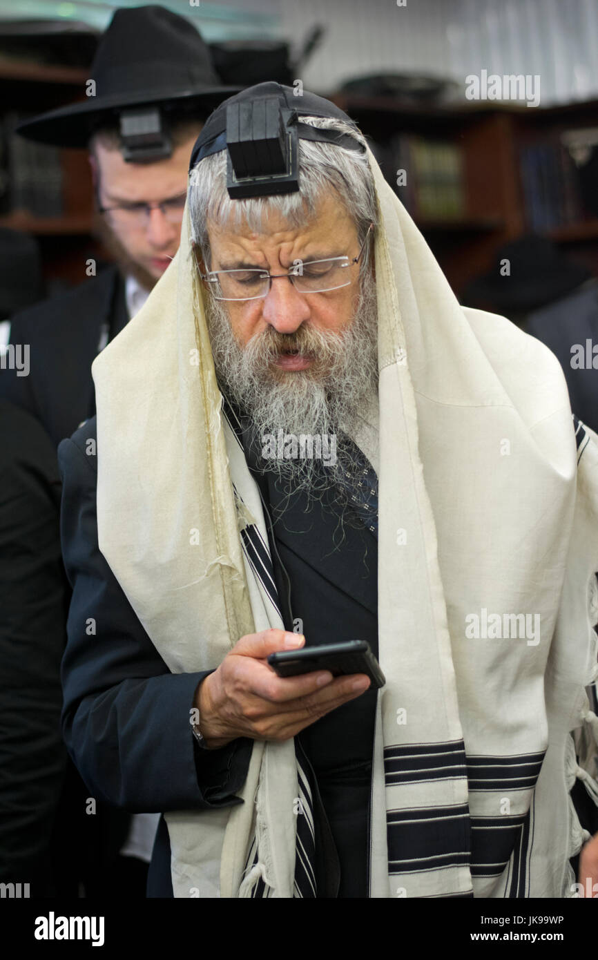 A religious Jewish man reciting his prayers from a phone instead of a prayer book. In Cambria Heights, Queens, New - Stock Image