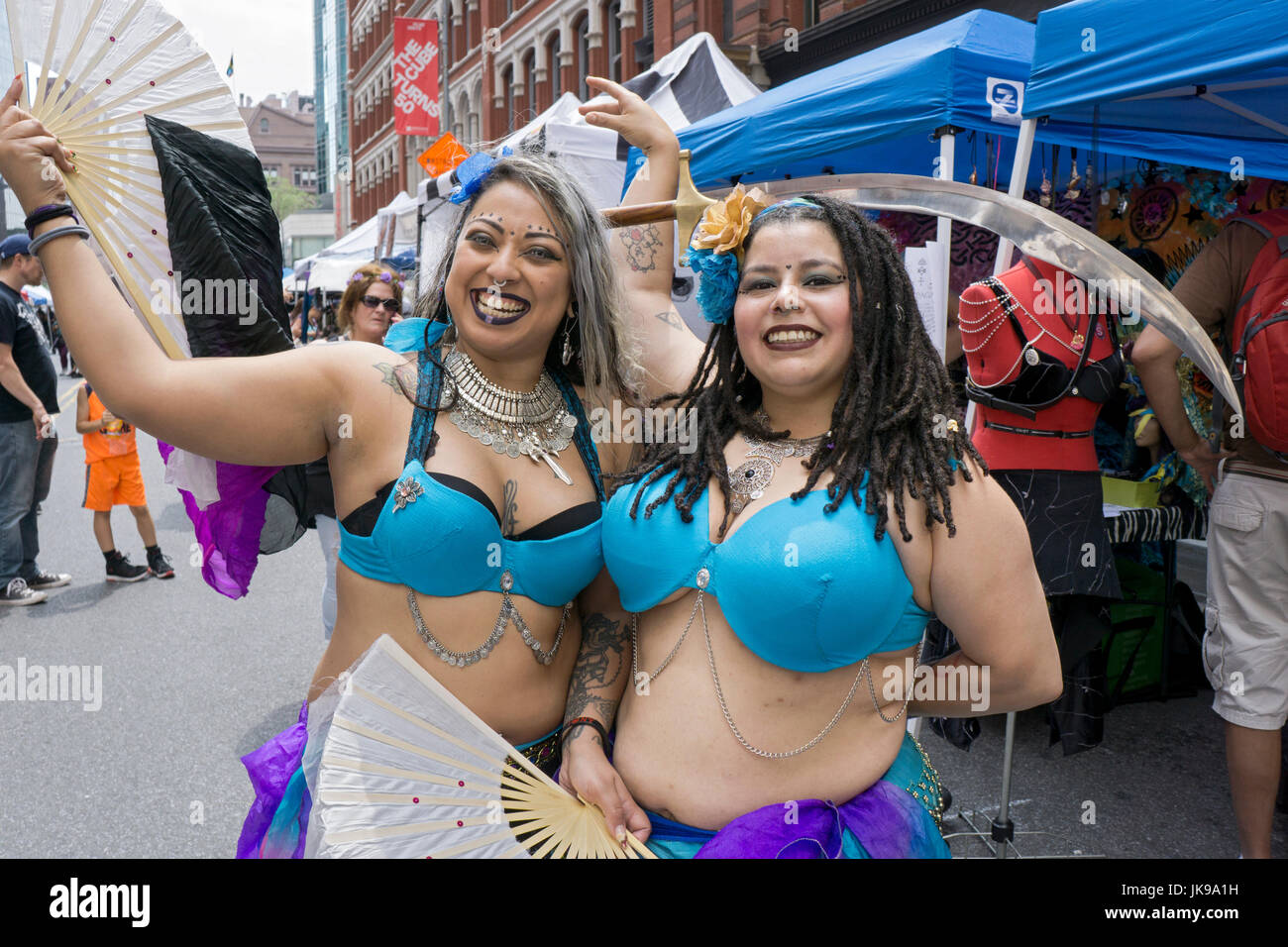 Two belly dancers in the same outfits pose for a photo at Witchsfest on Astor Place in Greenwich Village, New York - Stock Image