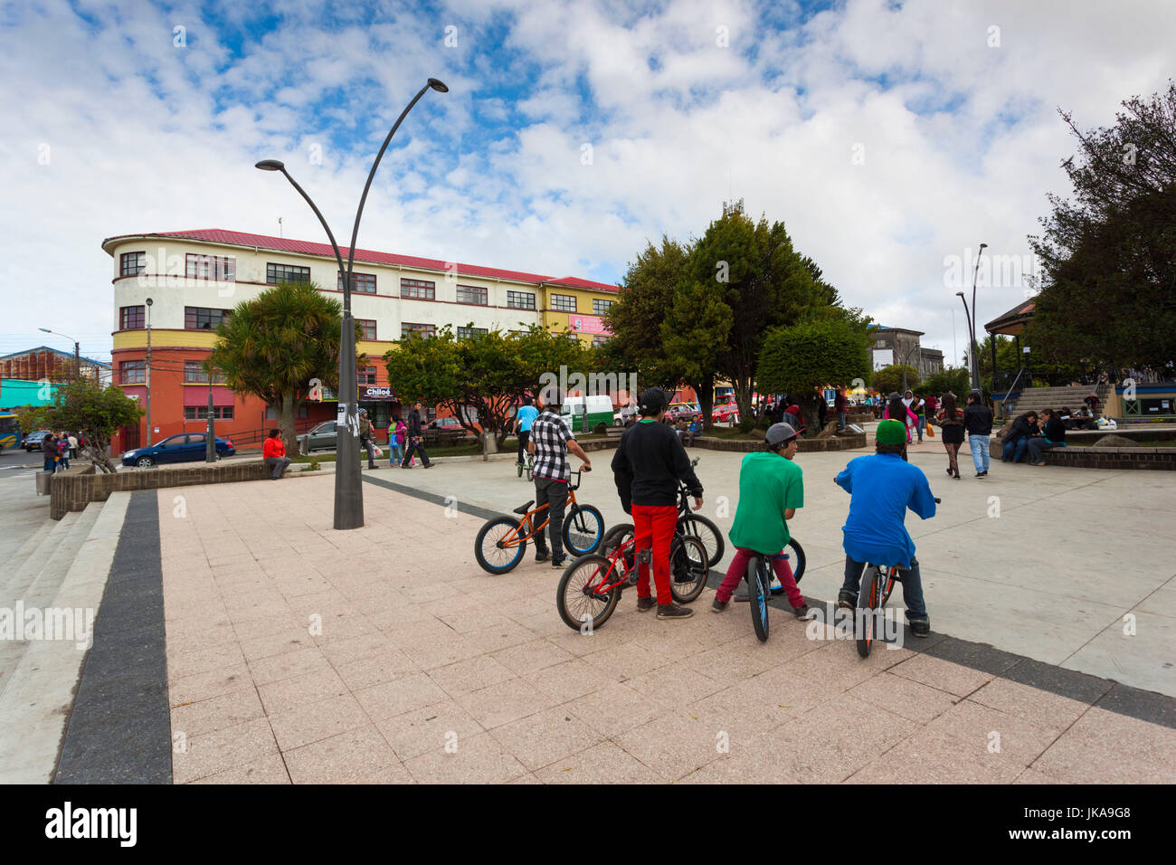 Chile, Chiloe Island, Ancud, bicyclists, town plaza - Stock Image