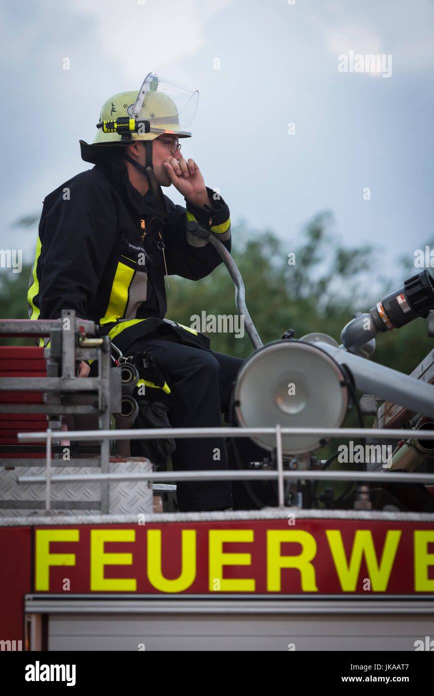 Feuerwehrmann blickt auf die großen Flammen des Sonnwendfeuers der Freiwilligen Feuerwehr Hallbergmoos - Stock Image