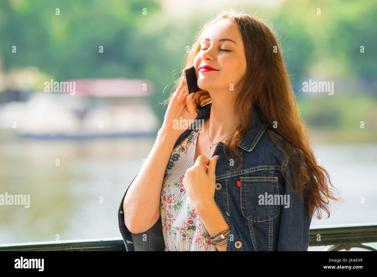 Portrait of the beautiful fashionable girl with smart phone in summer day Stock Photo