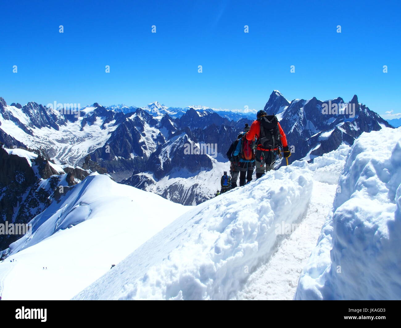 Four alpinists and mountaineer climber on AIGUILLE DU MIDI, CHAMONIX MONT BLANC french ALPS, top alpine mountains - Stock Image