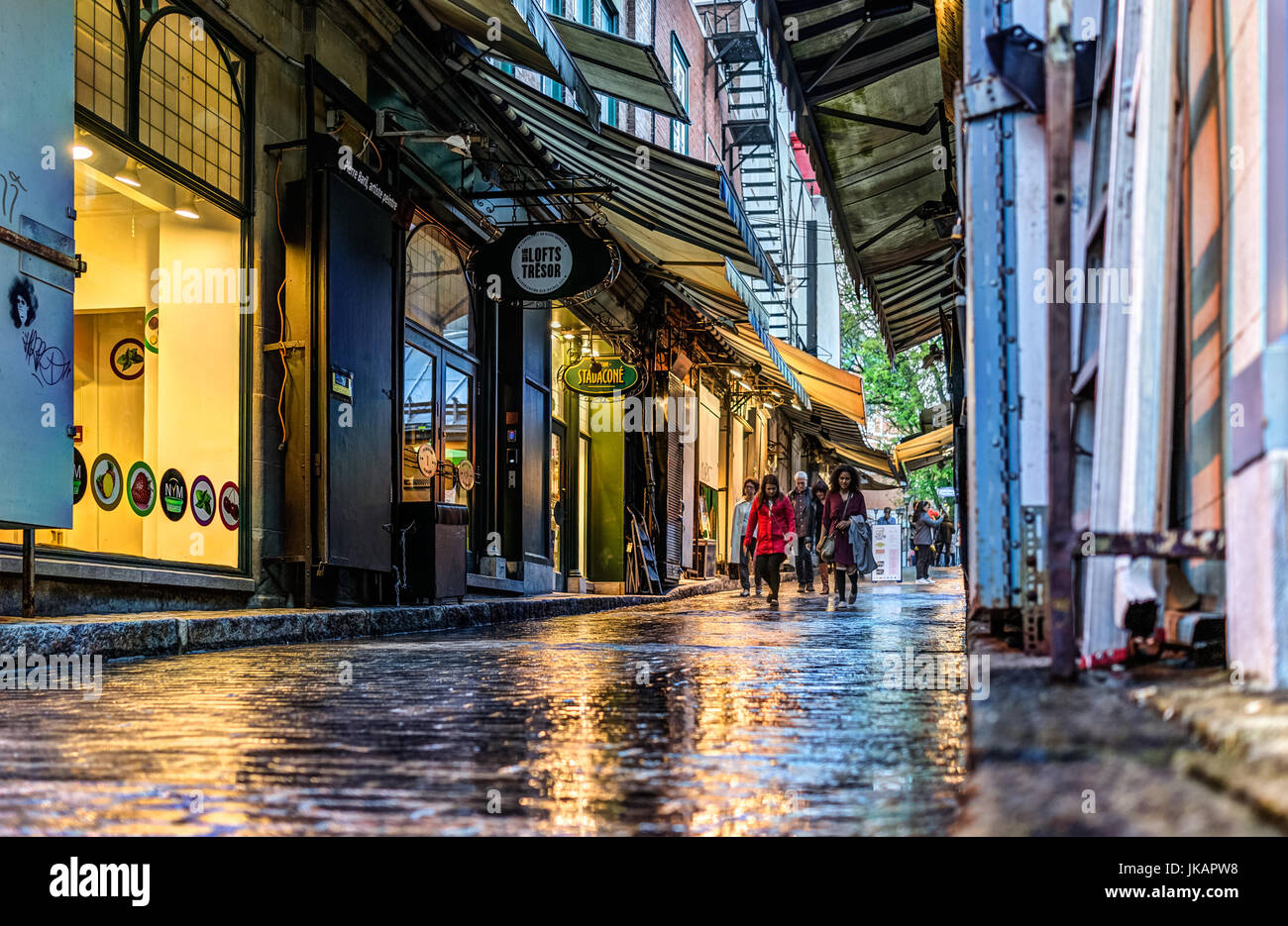 Quebec City, Canada - May 31, 2017: Old town street called Rue Tresor with shops and people walking on wet sidewalk Stock Photo