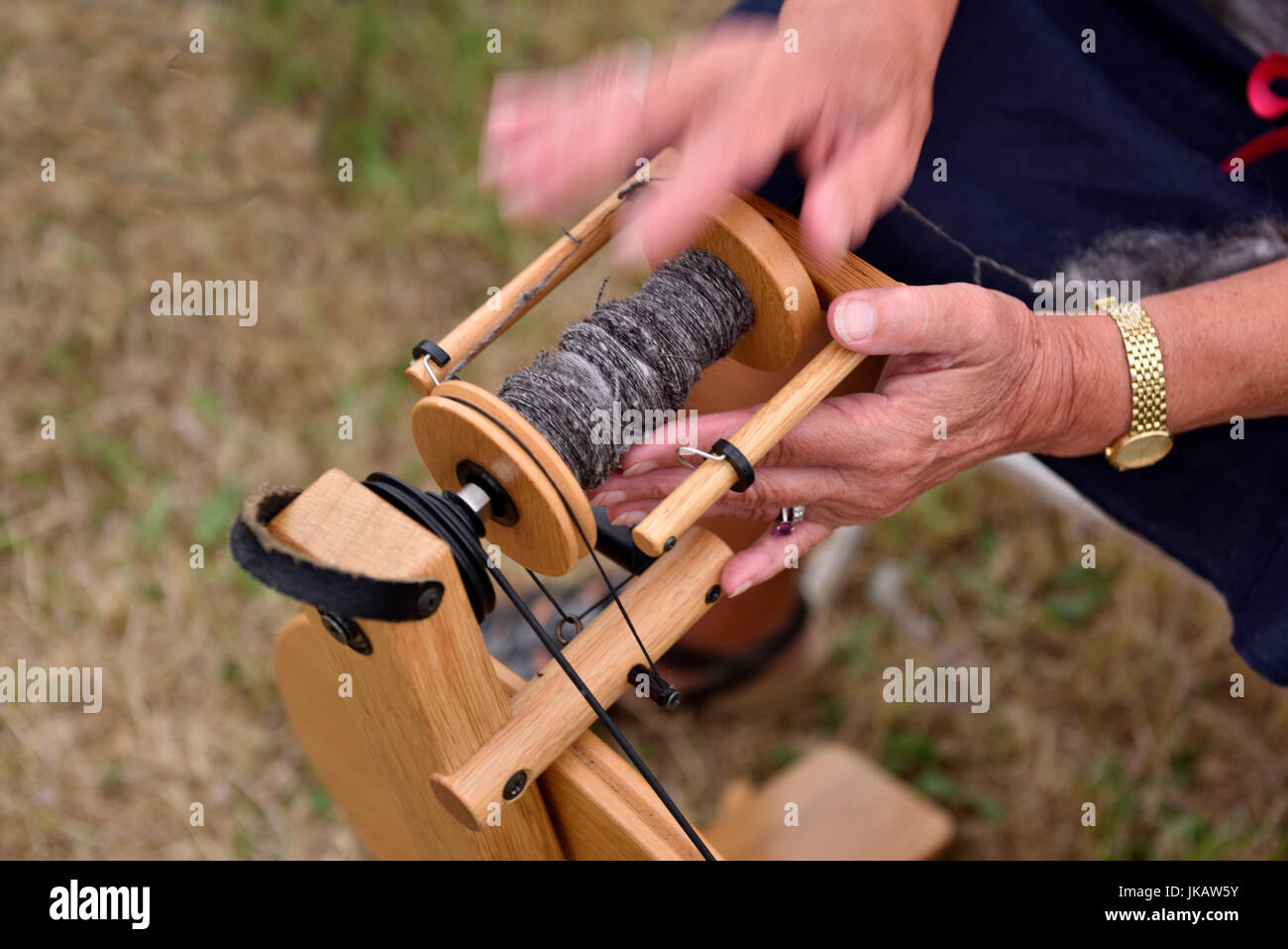 Close-up of woman's hands guiding thread on spinning wheel bobbin - Stock Image