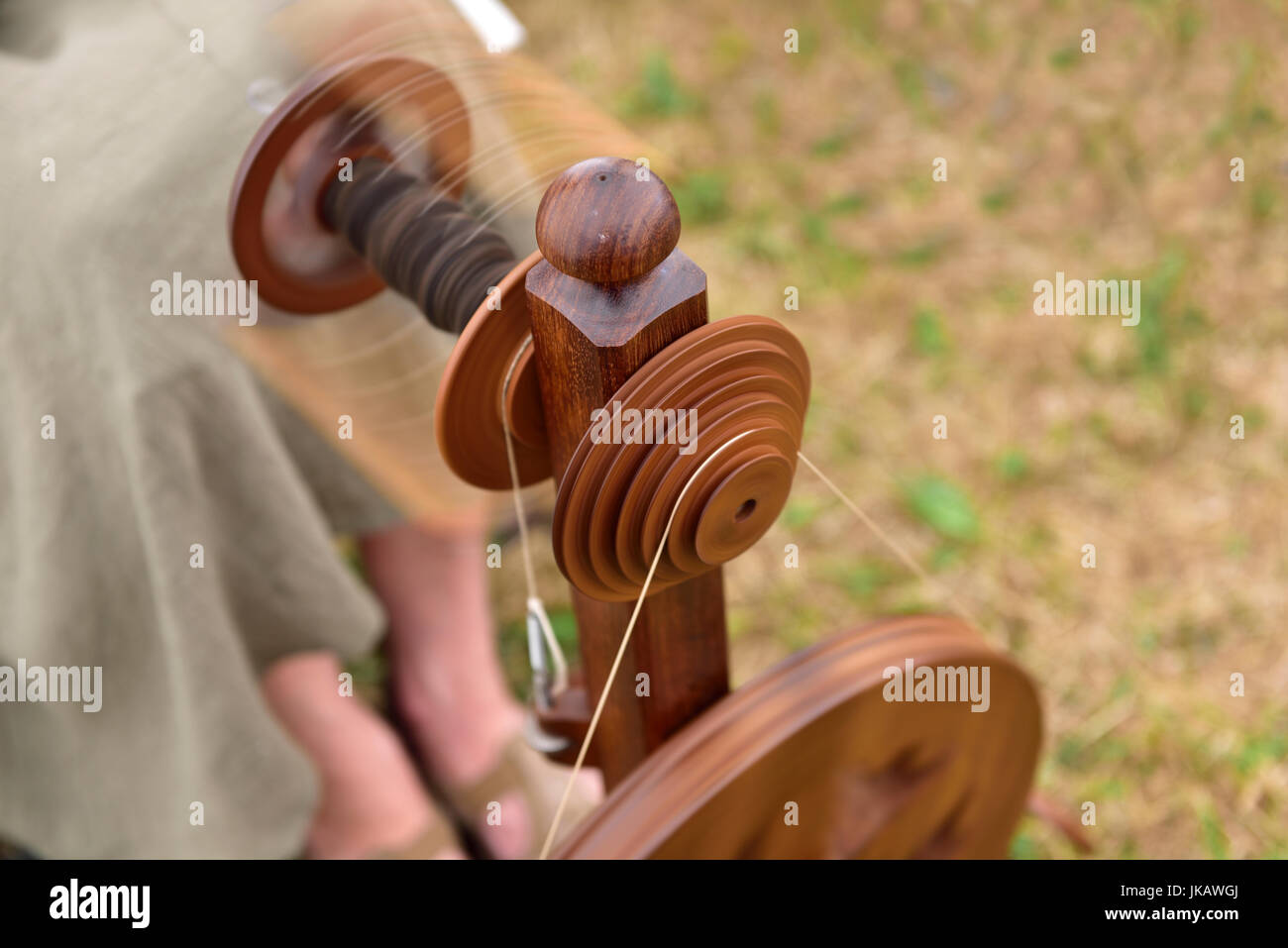 Close-up of bobbin pulley on spinning wheel bobbin with motion blur - Stock Image