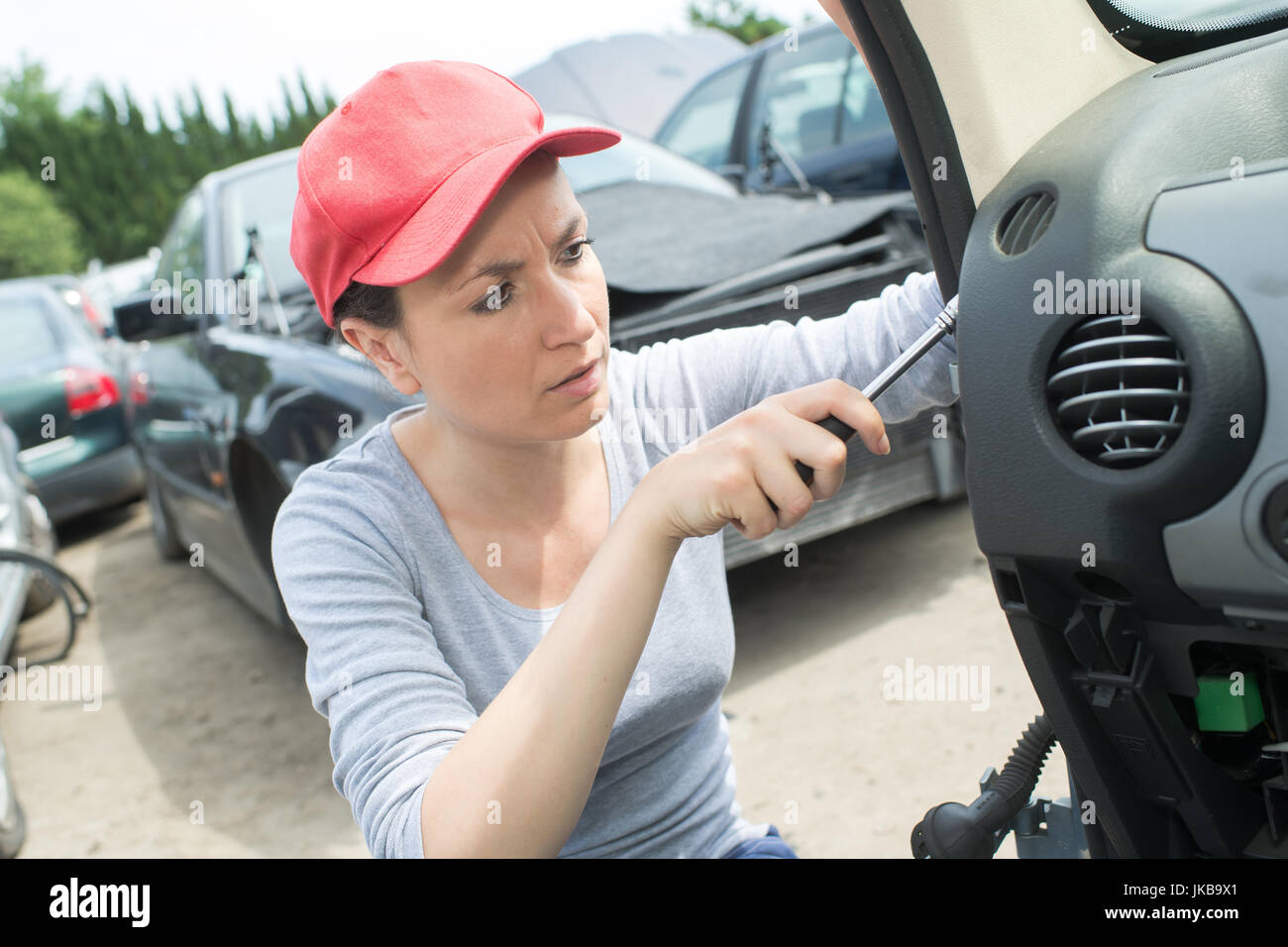 female mechanic removing parts on used cars at junk yard Stock Photo ...