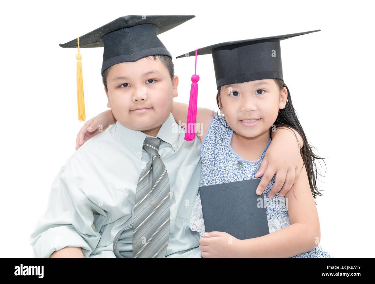 handsome boy and cute girl with graduate cap isolated on white background, education concept - Stock Image