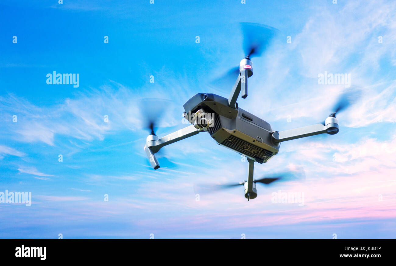 Drone in Flight over a blue sky background - Stock Image