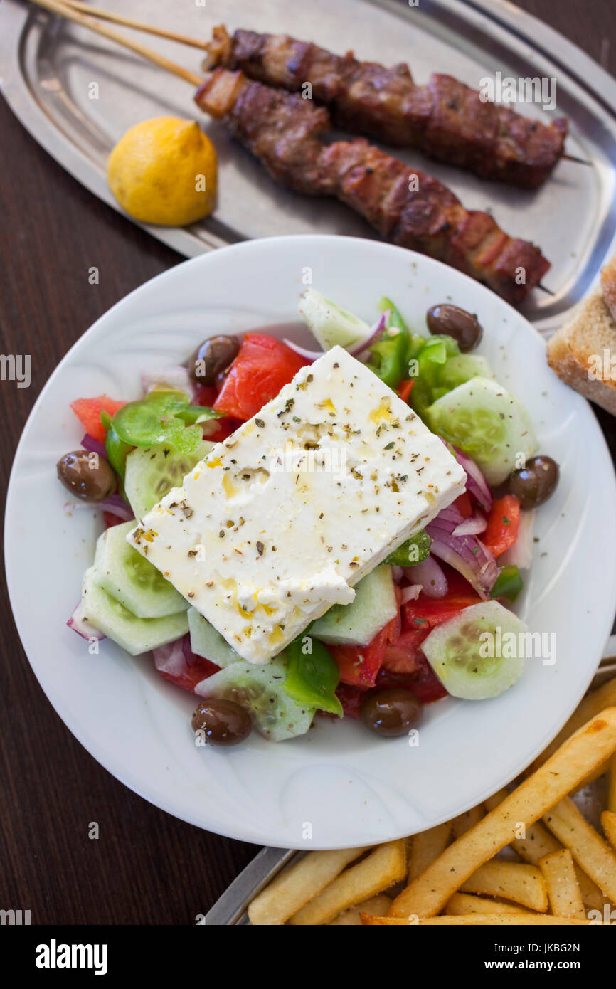 Greece, Peloponese Region, Corinth, Greek Salad and Souvlaki with French Fries - Stock Image