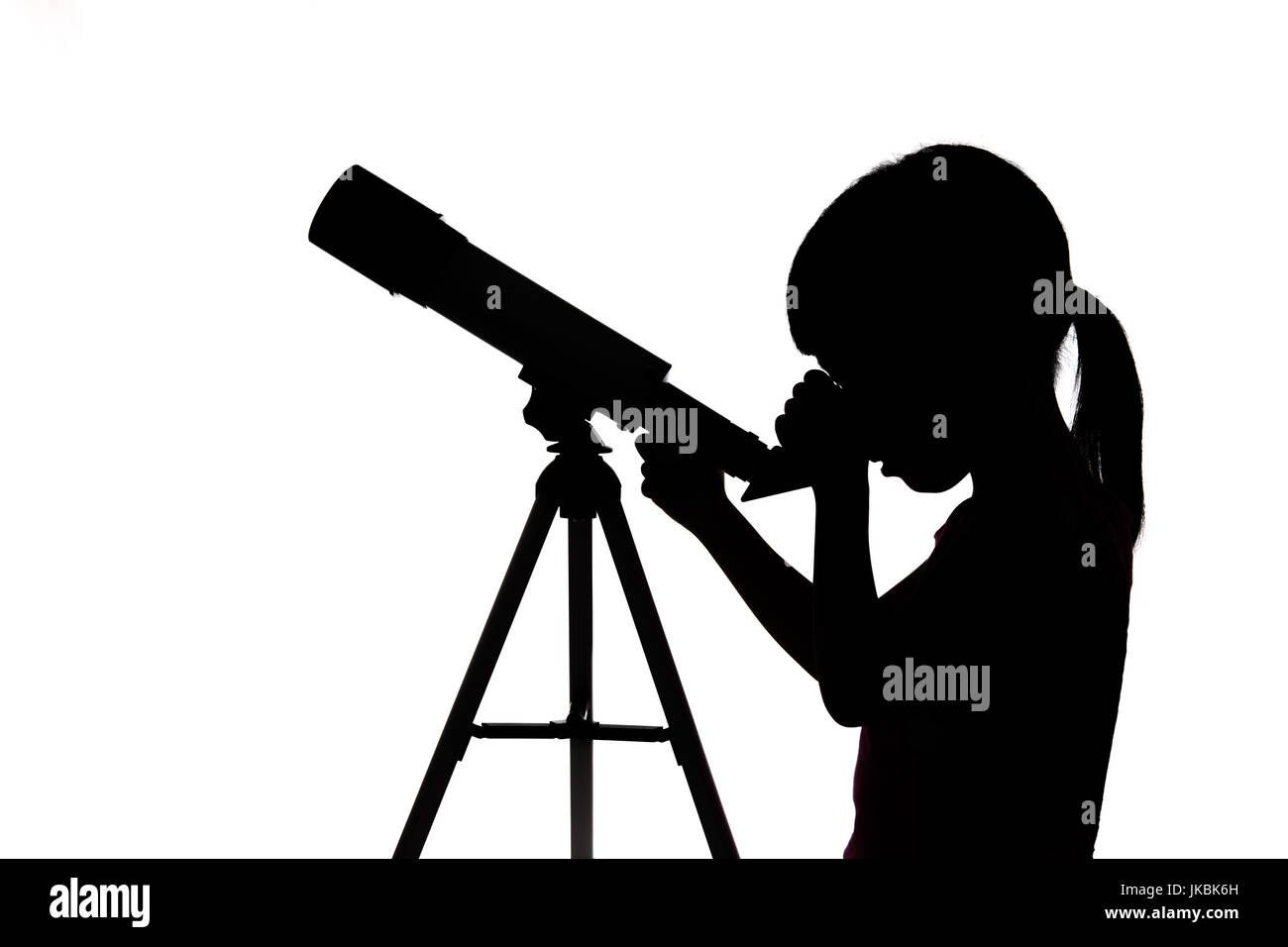 Silhouette of little girl looking through a telescope in isolated white background - Stock Image