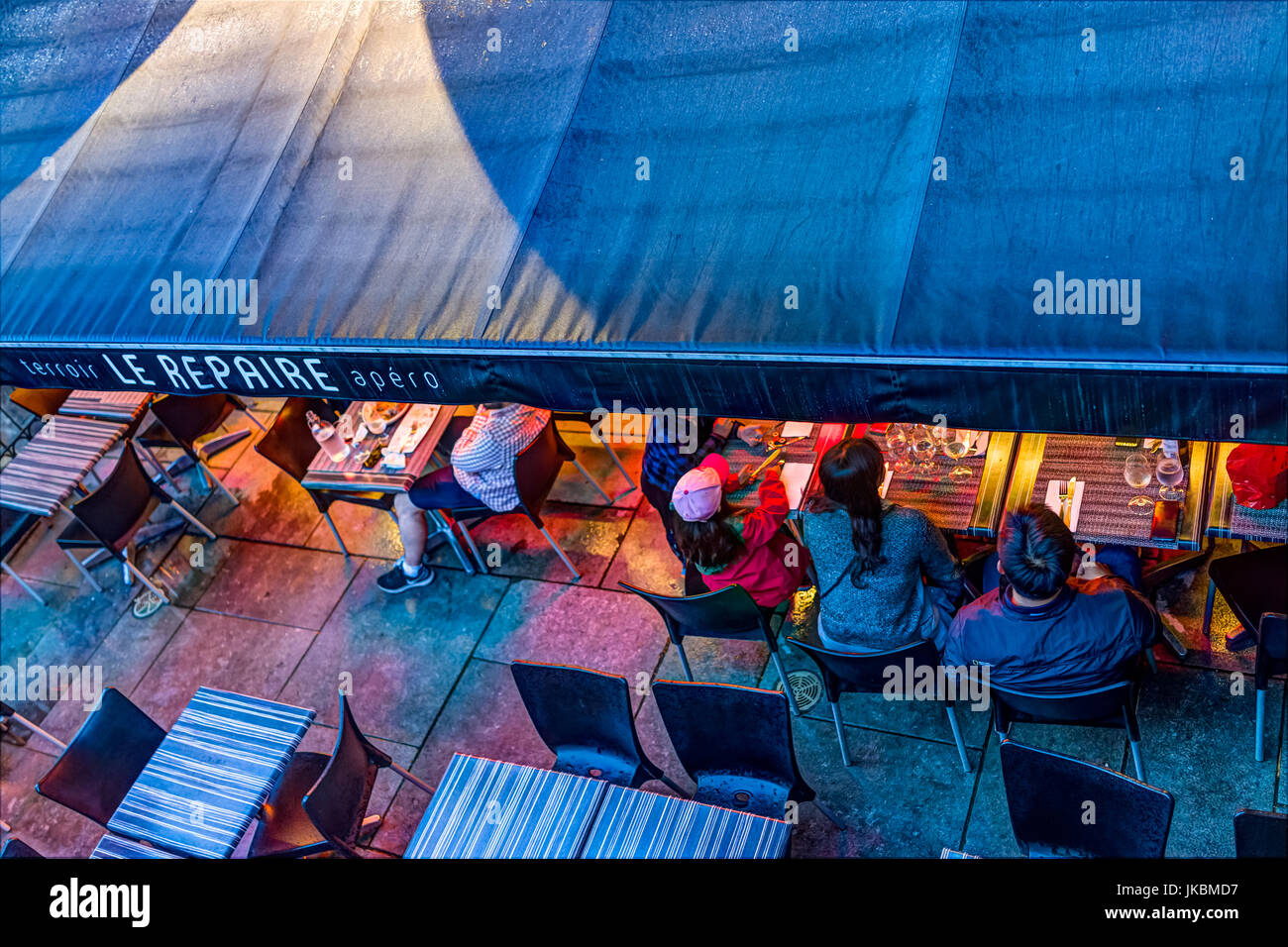 Quebec City, Canada - May 31, 2017: Le Repaire restaurant sign and people sitting, eating on outdoor tables during - Stock Image