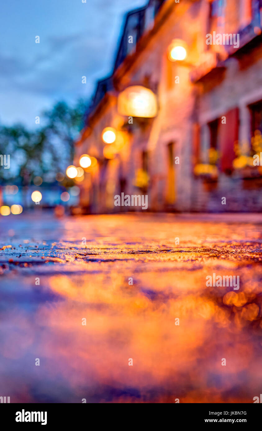 Macro closeup of colorful, vibrant and cobblestone street at night after rain with reflection of lights - Stock Image
