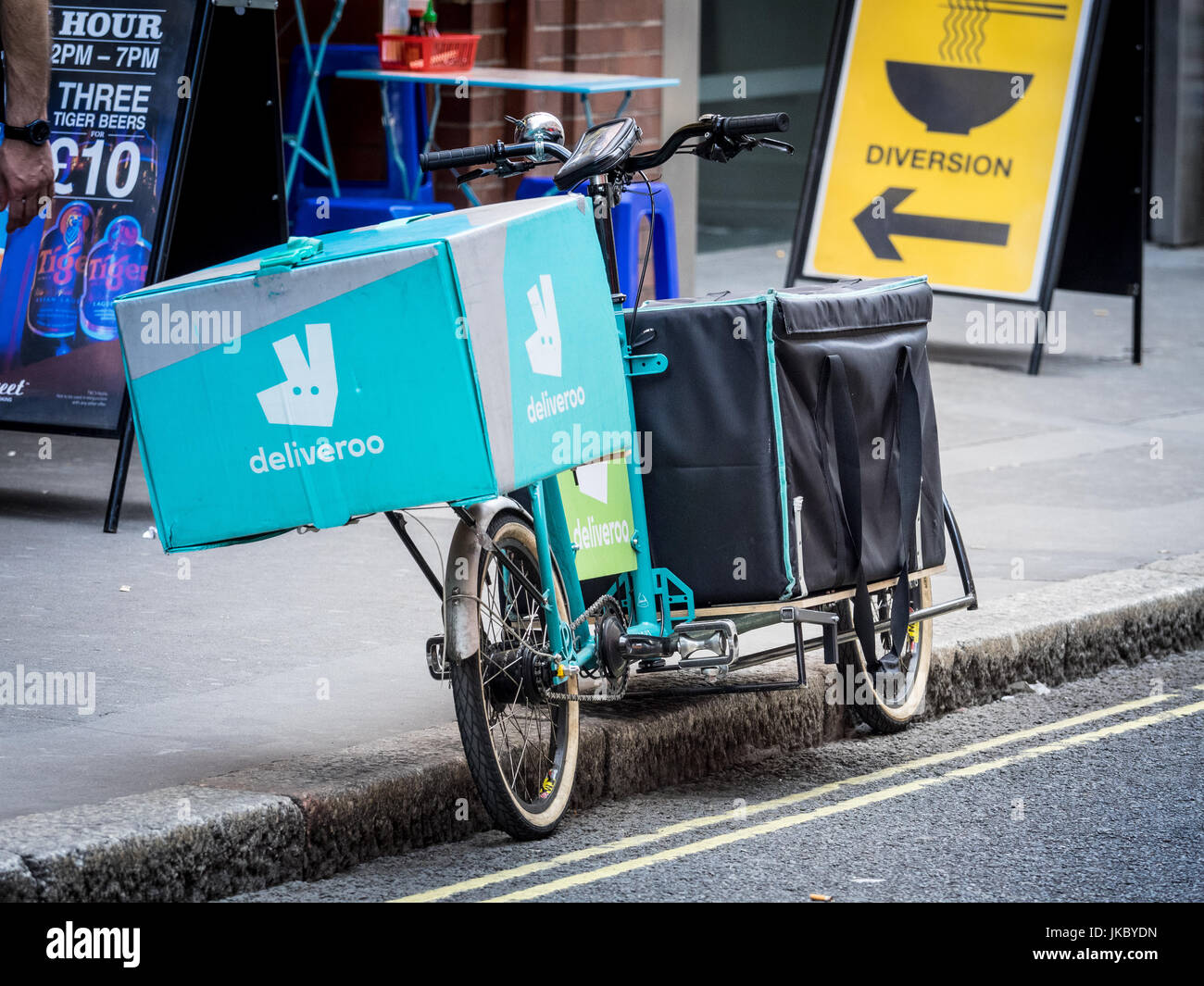 Deliveroo Cargo Bike - a Deliveroo Food Delivery Courier cargo bike parked outside a restaturant in central London Stock Photo