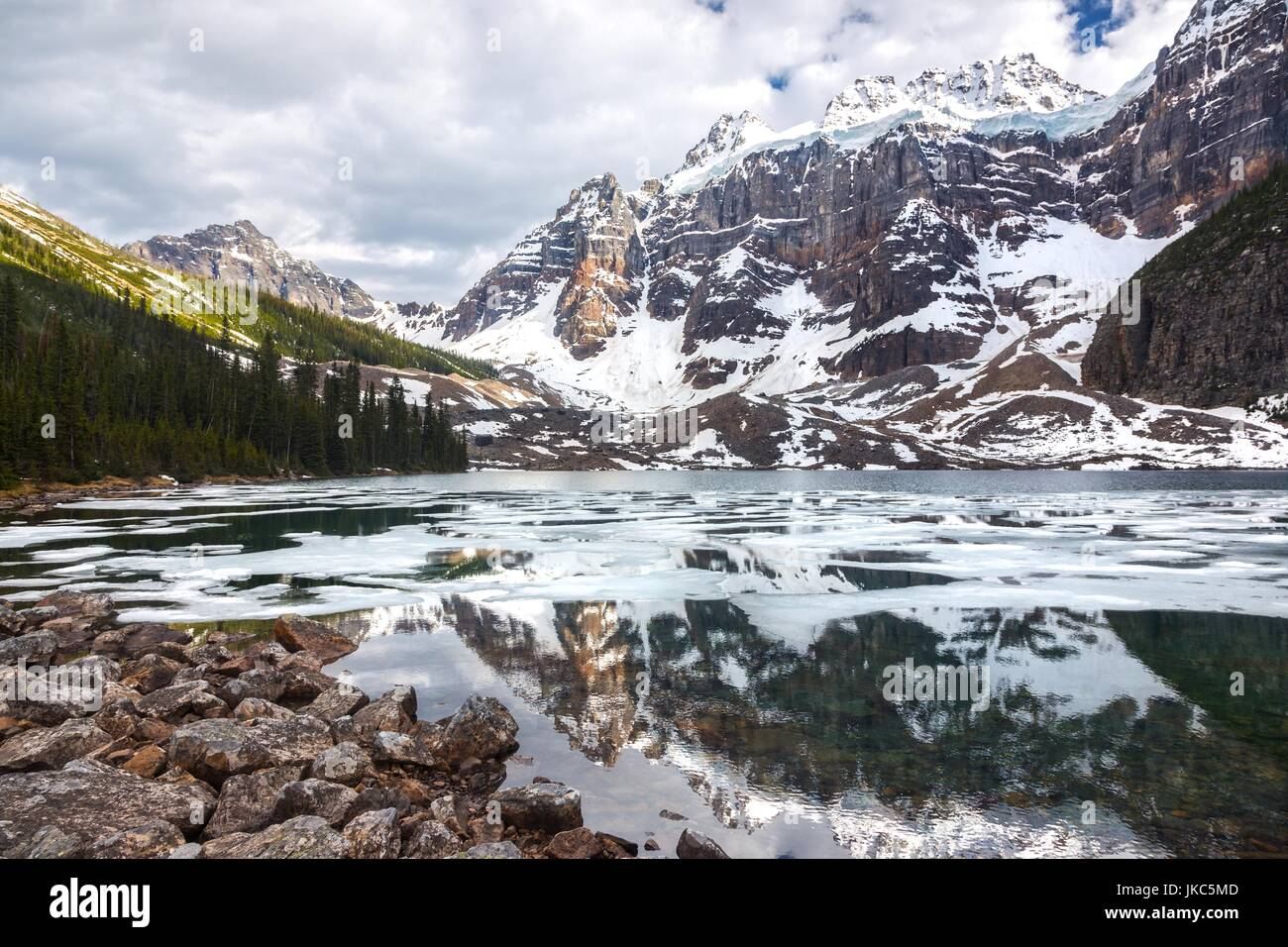 Upper Consolation Lake Melting in late Spring  with Mount Quadra in Background, Banff National Park Rocky Mountains Stock Photo